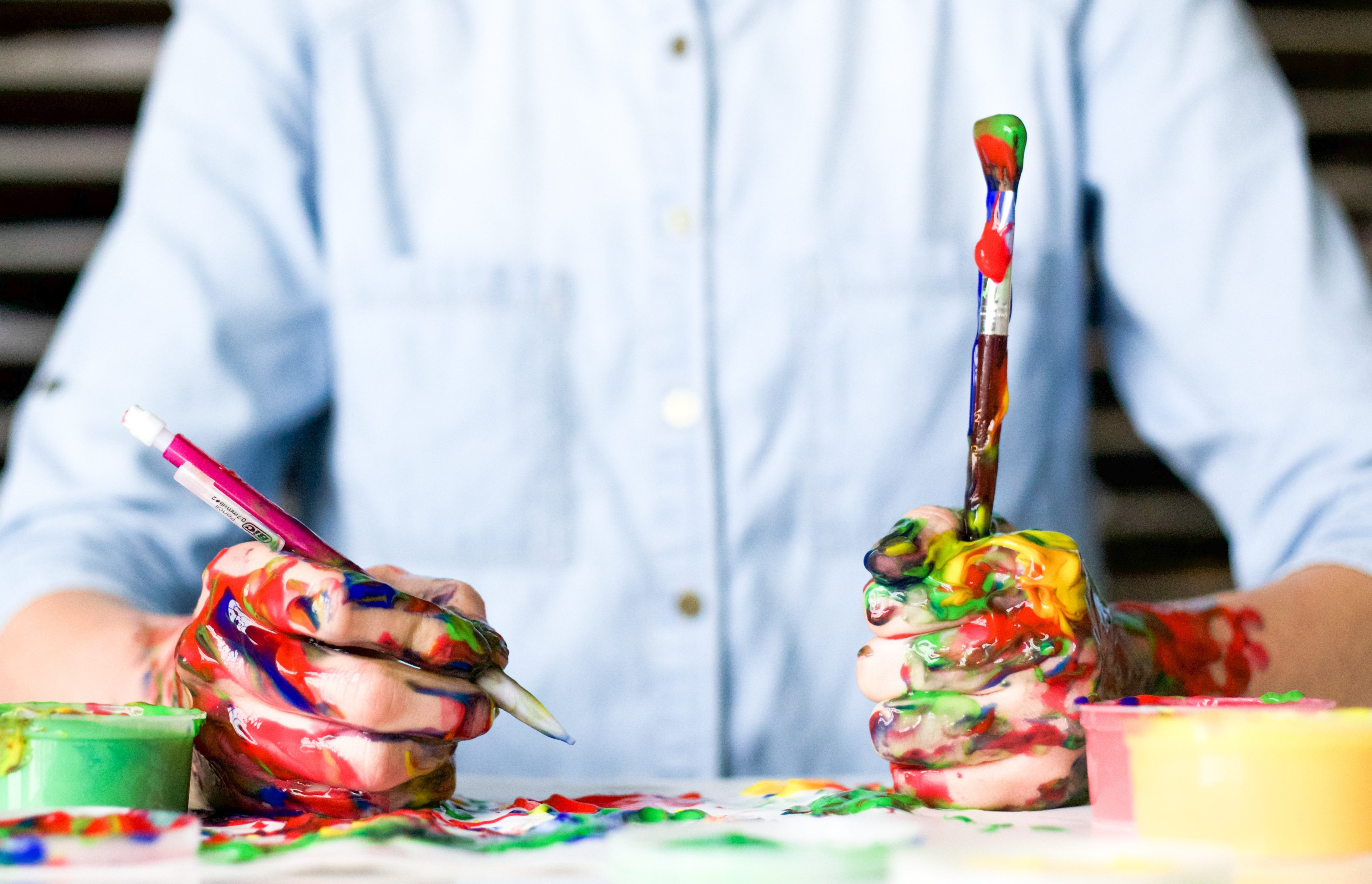 A person sits at a table with a pencil and paintbrush in their hands. Their hands and the materials are dripping in multicolored paint. It appears to be a child.