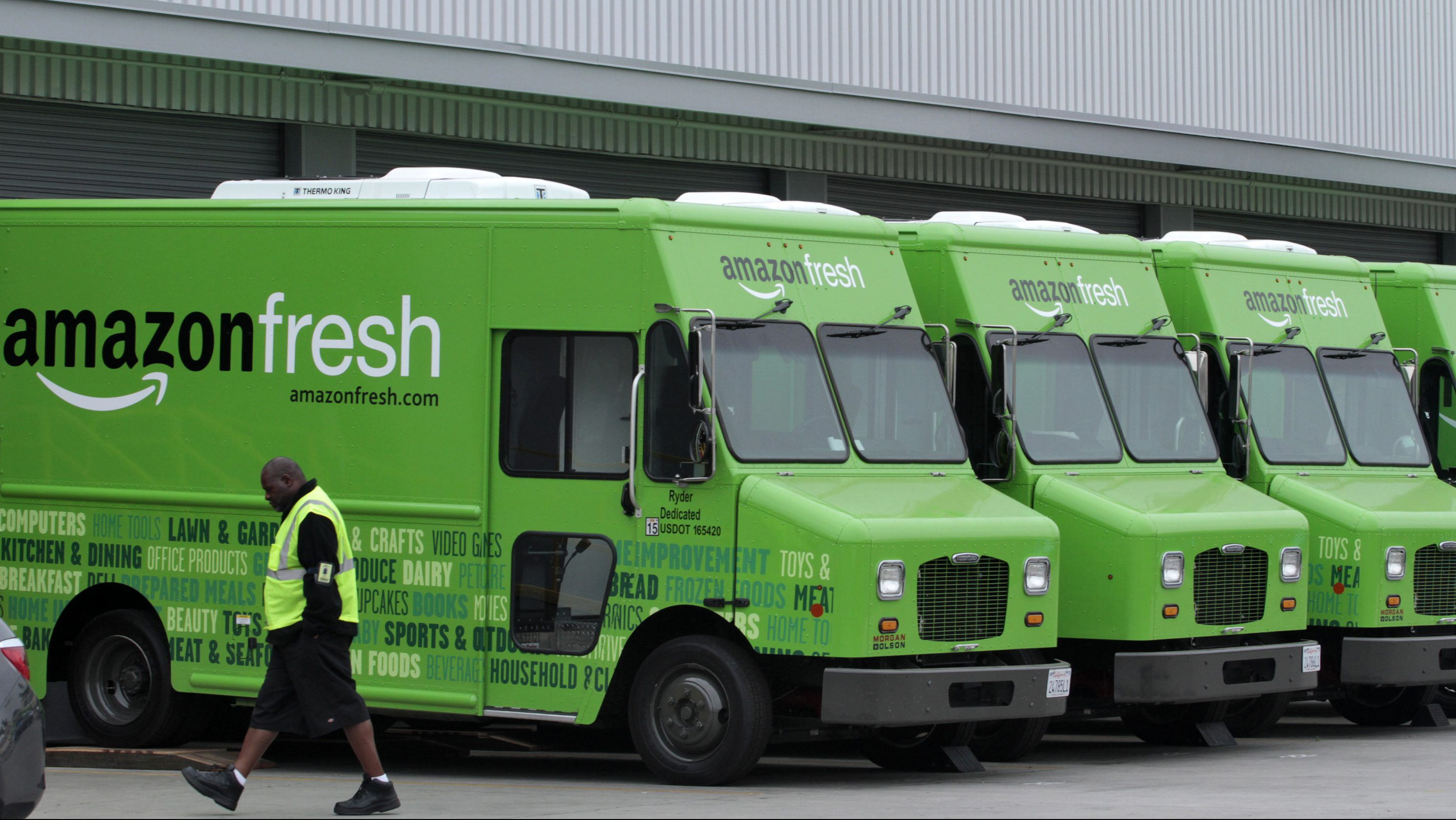 A worker walks past Amazon Fresh delivery vans parked at an Amazon Fresh warehouse in Inglewood, California, June 14, 2013. The online grocery start-up Webvan is rising from the dead--in the form of an online grocery business called Amazon Fresh. Picture taken June 14, 2013.