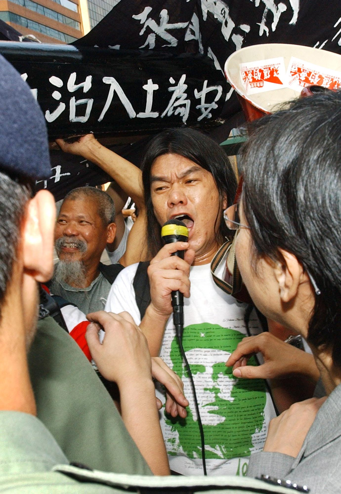 "Wearing his trademark Che Guevara t-shirt, Hong Kong activist ""Longhair"" Leung Kwok-hung shouts into a bullhorn during a protest in Hong Kong, July 1, 2004. The veteran gadfly is now hoping to take his message inside the halls of power by running for a legislative seat. Leung, who fell about 7,700 votes short in the last legislative election four years ago, believes massive anti-government sentiment will carry him to victory in the Sept. 12 contest."
