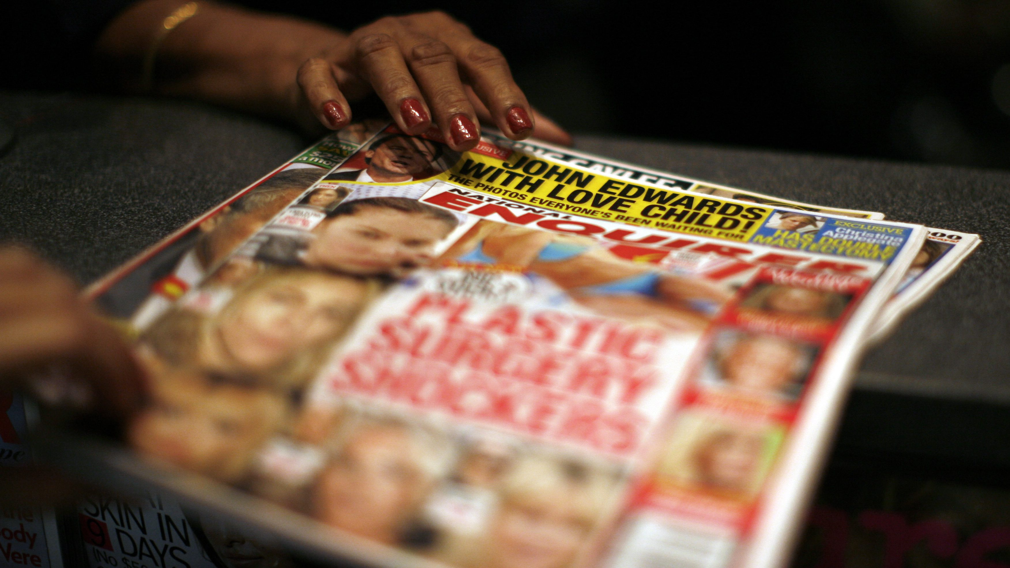 A commuter purchases a copy of the National Enquirer in a newsstand in New York's Penn Station Friday Aug. 8, 2008. The tabloid first reported Former Democratic presidential candidate John Edwards having an extramarital affair while his wife was battling cancer. (AP Photo/Ed Ou)