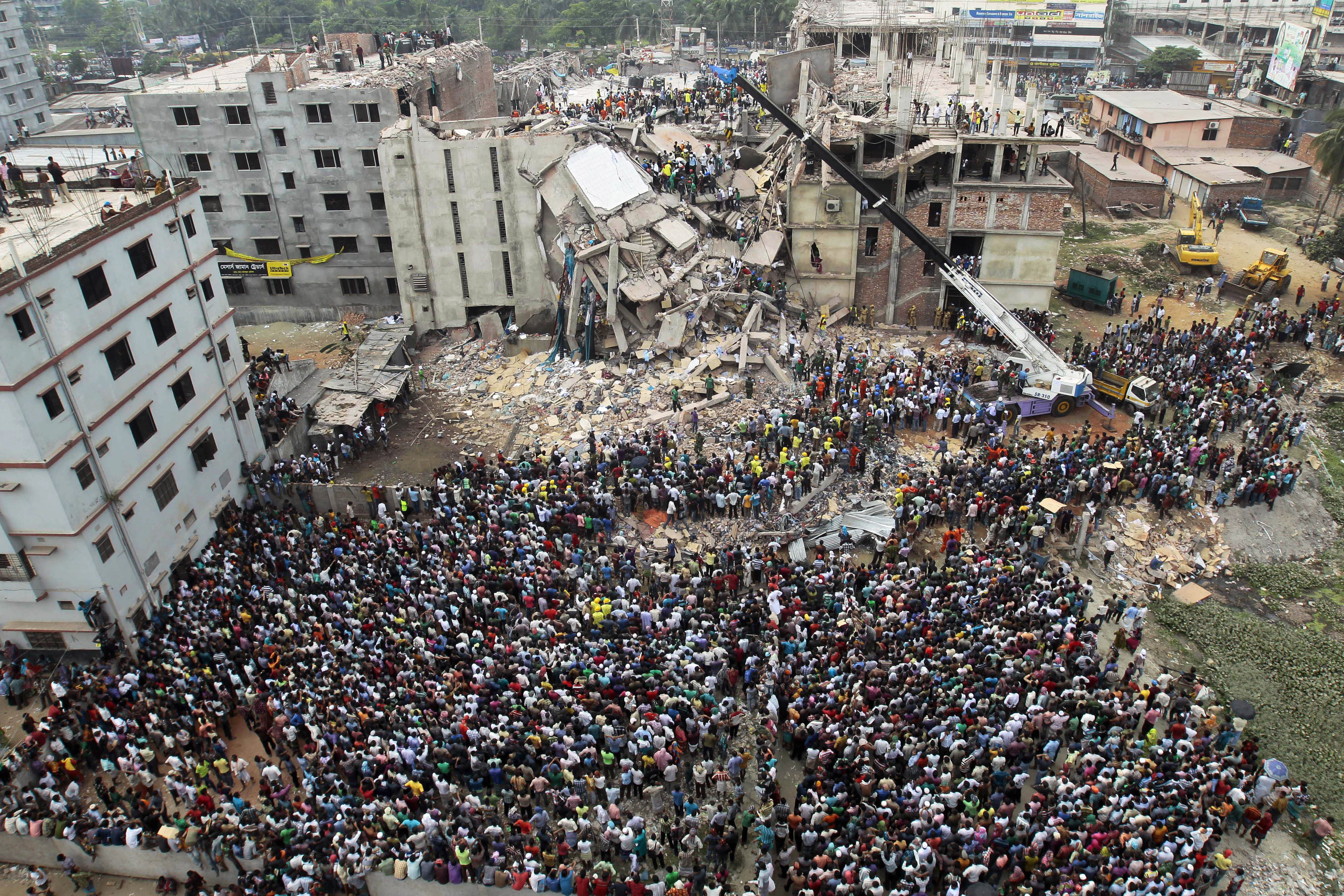 FILE - In this April 25, 2013, file photo, Bangladeshi people gather as rescuers look for survivors and victims at the site of a building that collapsed a day earlier, in Savar, near Dhaka, Bangladesh. A Bangladesh court on Monday, July 18, 2016, indicted 41 people for murder in the 2013 deaths of more than 1,100 people in the collapse of a building that housed five garment factories outside the capital. (AP Photo/A.M.Ahad, File)