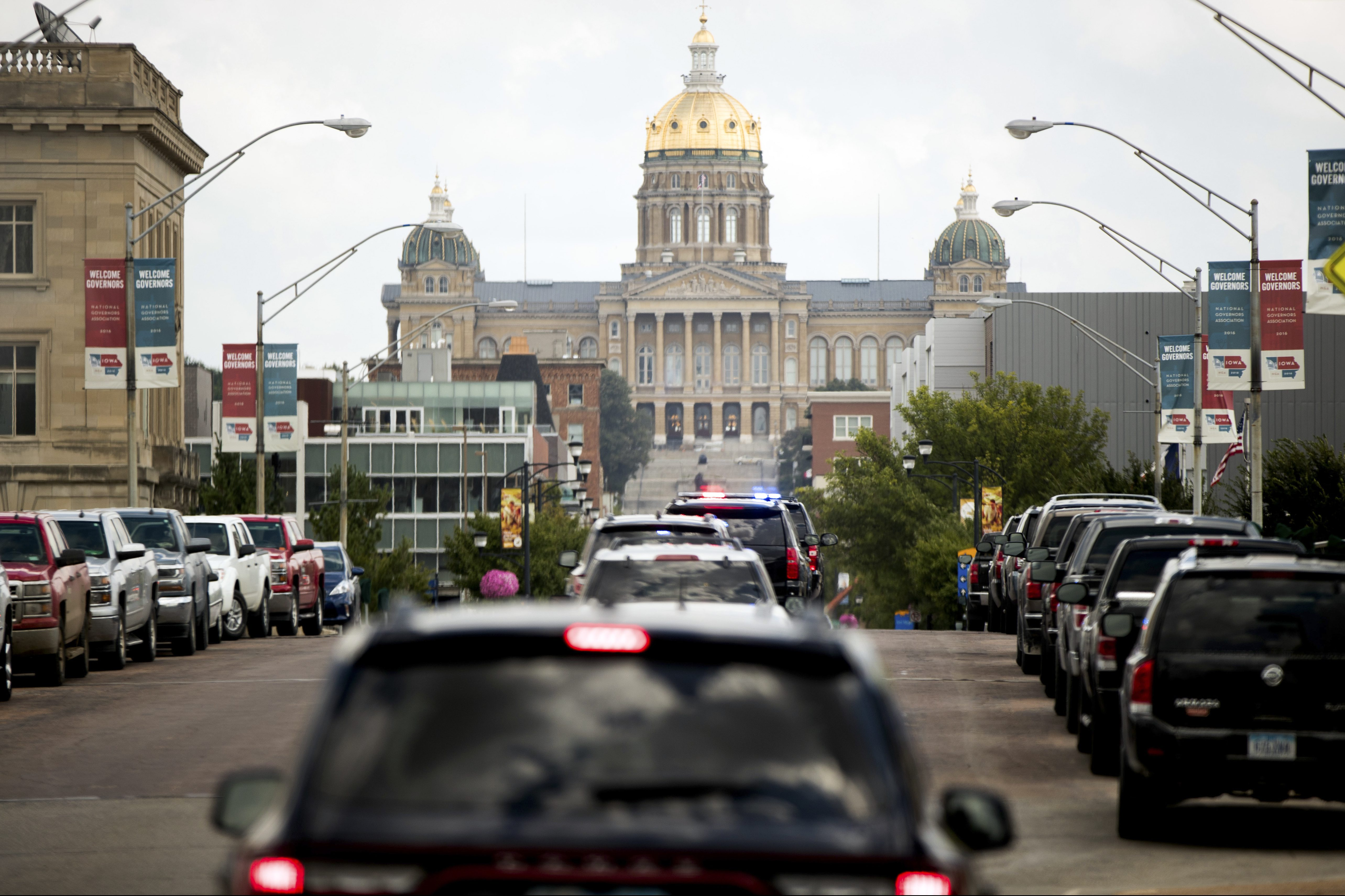The Iowa State Capitol Building is visible in the background as the motorcade carrying Democratic presidential candidate Hillary Clinton heads towards Raygun, a printing, design and clothing company, in Des Moines, Iowa, Wednesday, Aug. 10, 2016. (AP Photo/Andrew Harnik)