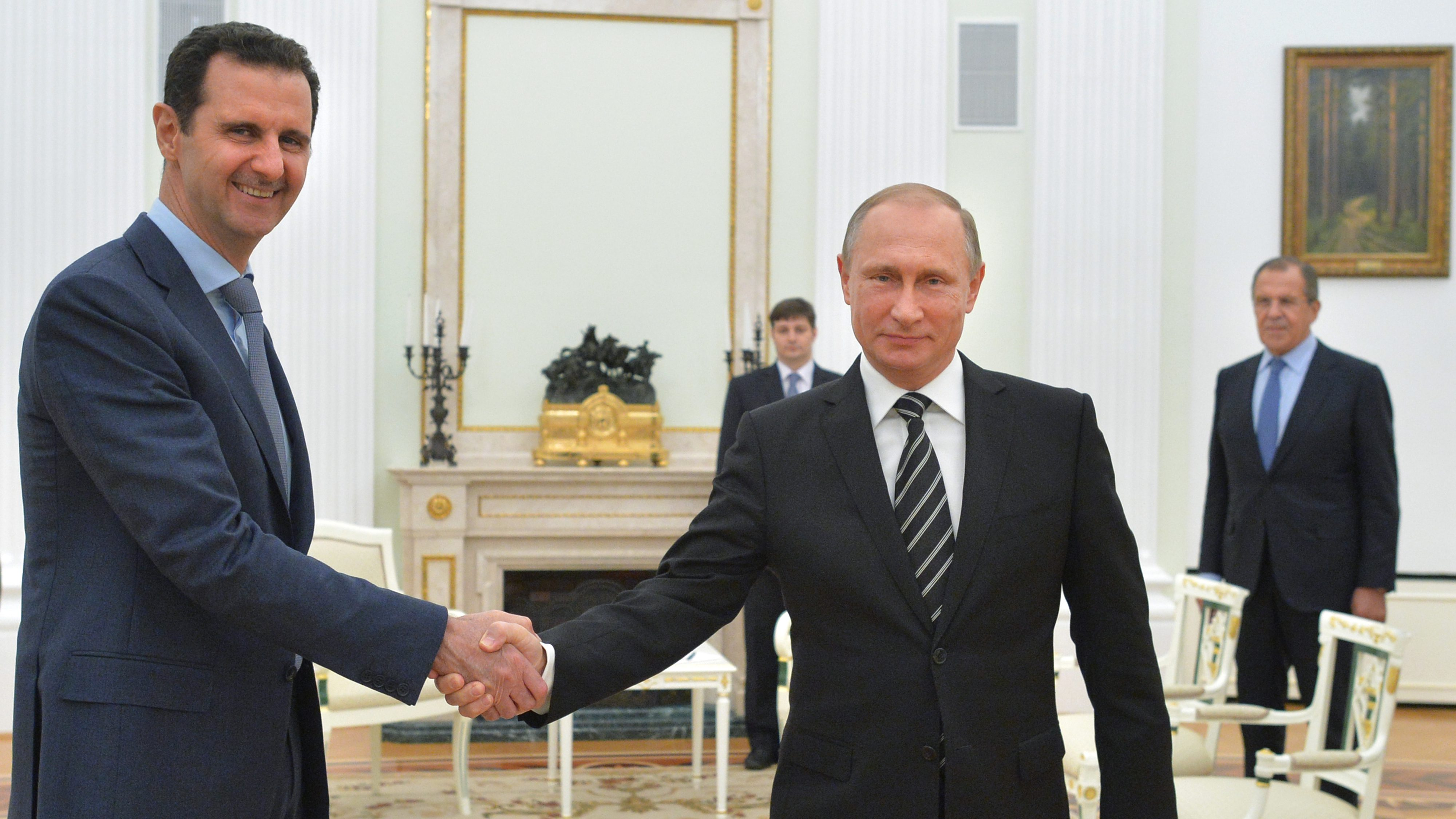 FILE - In this Oct. 20, 2015 file photo, Russian President Vladimir Putin, center, shakes hand with Syrian President Bashar Assad as Russian Foreign Minister Sergey Lavrov, right, looks on, at the Kremlin, in Moscow, Russia. For five years fighting has raged in Syria -- a globally resonant nightmare kept going in part by the insistence of Bashar Assad's opponents that he must go even though they were failing to dislodge him from power. Now an inflection point may finally be at hand, with increasingly important Turkey suggesting Assad could play a role in an unspecified transition period. (Alexei Druzhinin, RIA-Novosti, Kremlin Pool Photo via AP, File)