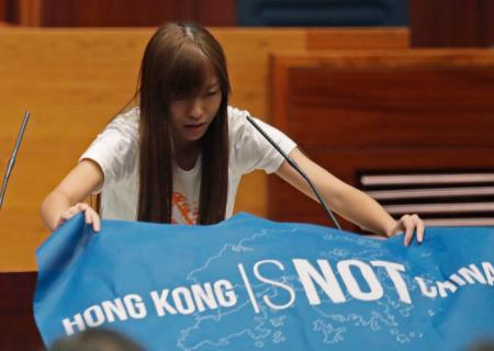 "Newly elected lawmake Yau Wai-ching of Youngspiration displays a banner with words reading ""Hong Kong is not China"" as she takes oath in the new legislature Council in Hong Kong, Wednesday, Oct. 12, 2016. A swearing-in ceremony to kick off Hong Kong's legislative session descended into farce Wednesday as newly elected pro-democracy lawmakers intentionally mangled their oaths in a show of defiance against Beijing. The new crop of lawmakers, elected last month amid swelling anti-China sentiment, object to the oath's requirement to pledge allegiance to the ""Hong Kong Special Administrative Region of the People's Republic of China"" and its Basic Law constitution."