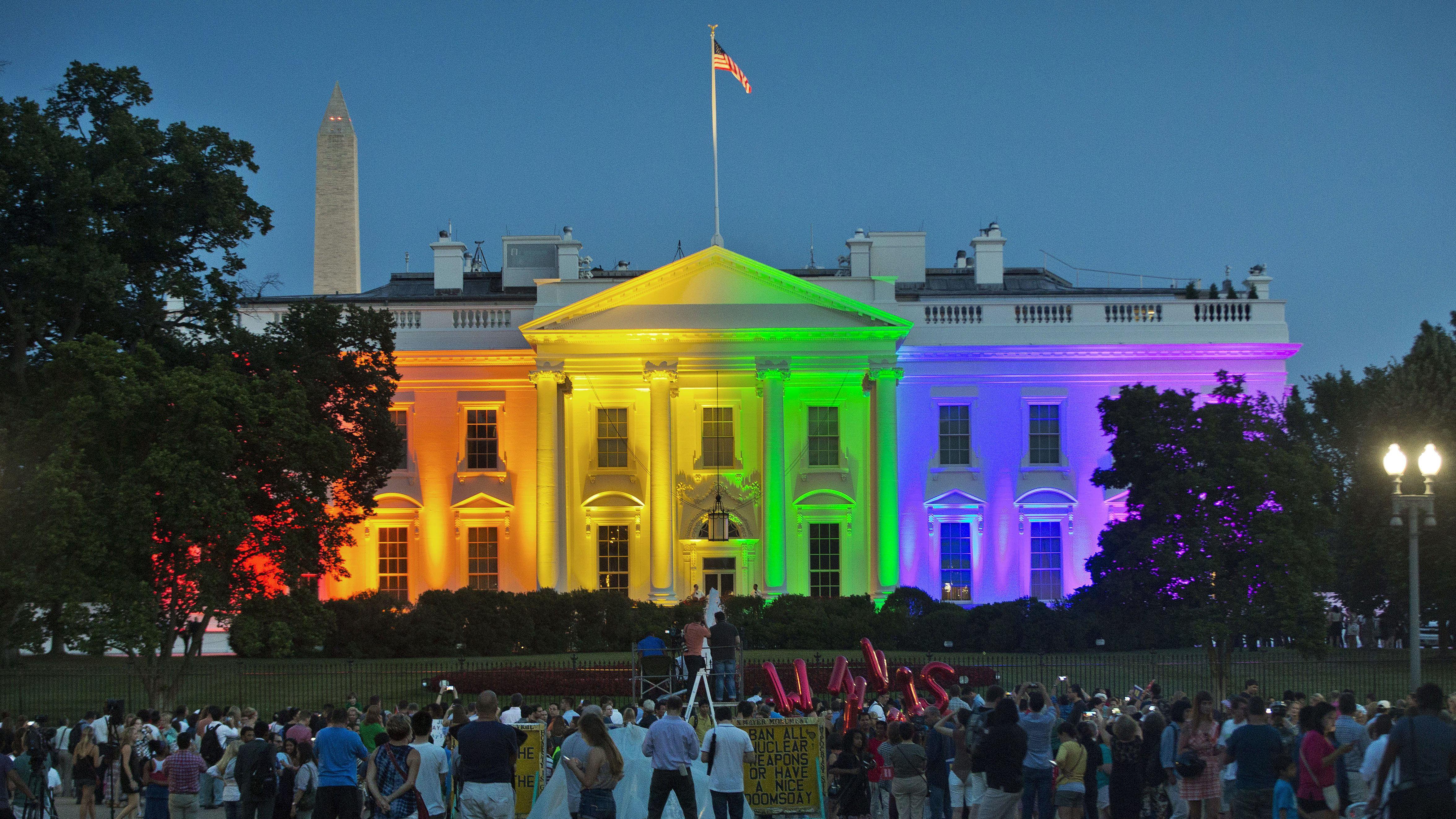 "FILE - In this Friday, June 26, 2015 file photo, people gather in Lafayette Park to see the White House illuminated with rainbow colors in commemoration of the Supreme Court's ruling to legalize same-sex marriage in Washington. It was a new look for the White House: illuminated in rainbow colors to celebrate the Supreme Court decision allowing same-sex marriage nationwide. President Barack Obama, who was inside, felt the glow on that June night in 2015. To see people gathered in the evening outside on a beautiful summer night, and to feel whole and to feel accepted, and to feel that they had a right to love _ that was pretty cool,"" he said a few days later. (AP Photo/Pablo Martinez Monsivais, File)"