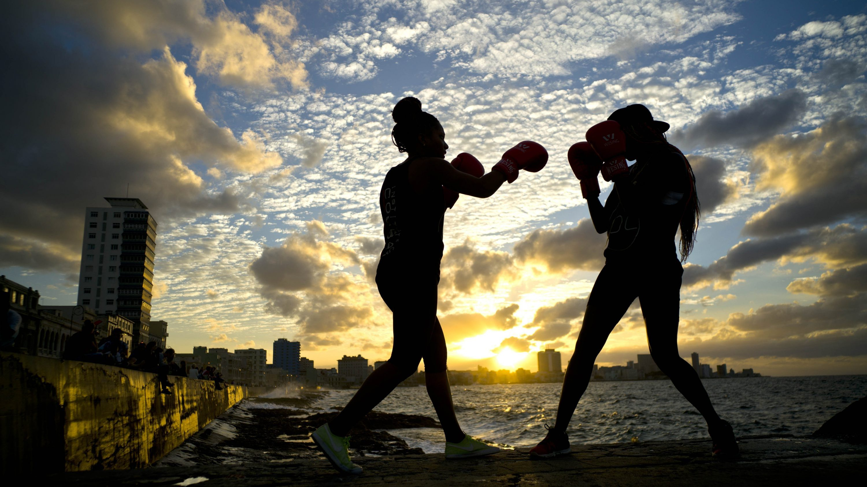 """In this Jan. 30, 2017 photo, boxers Idamelys Moreno, left, and Legnis Cala, train during a photo session on Havana's sea wall, in Cuba. Moreno and Cala are part of a group of up-and-coming female boxers on the island who want government support to form Cuba's first female boxing team and help dispel a decades-old belief once summed up by a former top coach: """"Cuban women are meant to show the beauty of their face, not receive punches."""""""