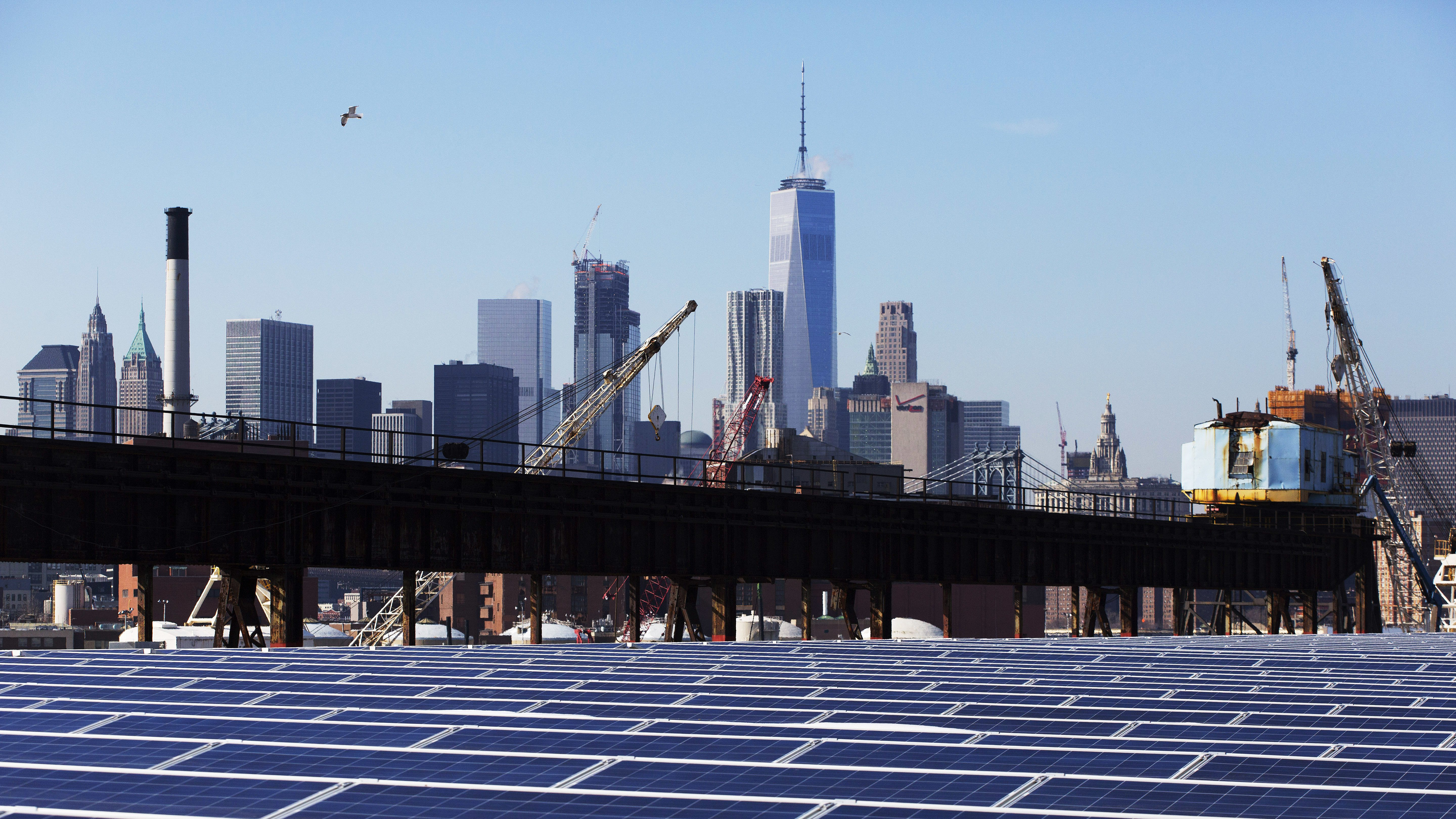 A rooftop is covered with solar panels at the Brooklyn Navy Yard, Tuesday, Feb. 14, 2017, in New York. The Manhattan skyline is at top. ConEdison Solutions installed 3,152 solar panels on the roof of Building 293 in 2016. The new panels will generate 1.1 million kilowatt hours of energy per year, according to the mayor's office. The New York State Energy Research and Development Authority provided more than $600,000 in incentives for the project. (AP Photo/Mark Lennihan)