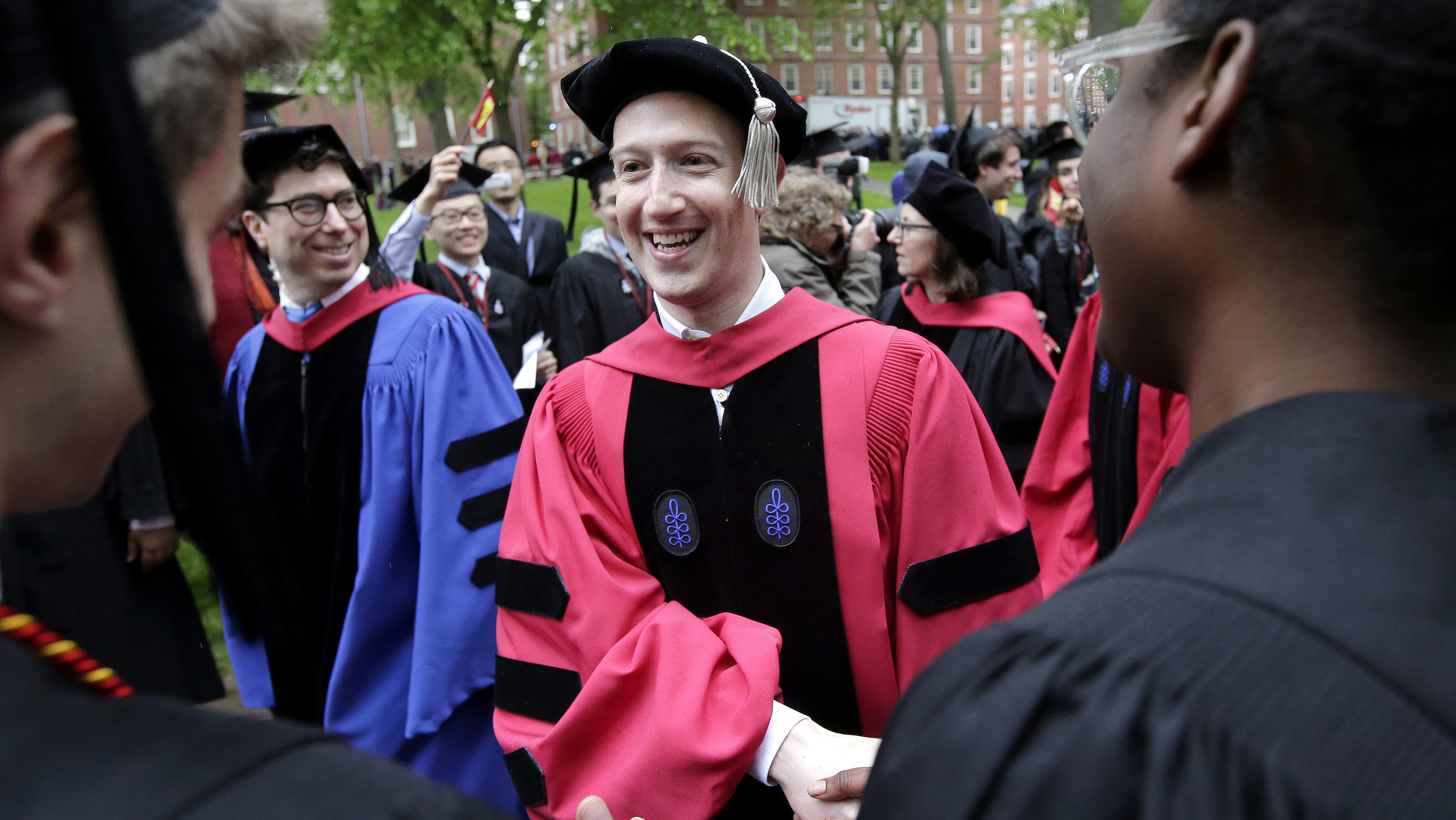 Facebook CEO and Harvard dropout Mark Zuckerberg, center, greets graduating Harvard students as he walks in a procession though Harvard Yard at the start of Harvard University commencement exercises, Thursday, May 25, 2017, in Cambridge, Mass. Zuckerberg is giving a commencement address at Harvard, where he dropped out 12 years ago to focus on Facebook. (AP Photo/Steven Senne)
