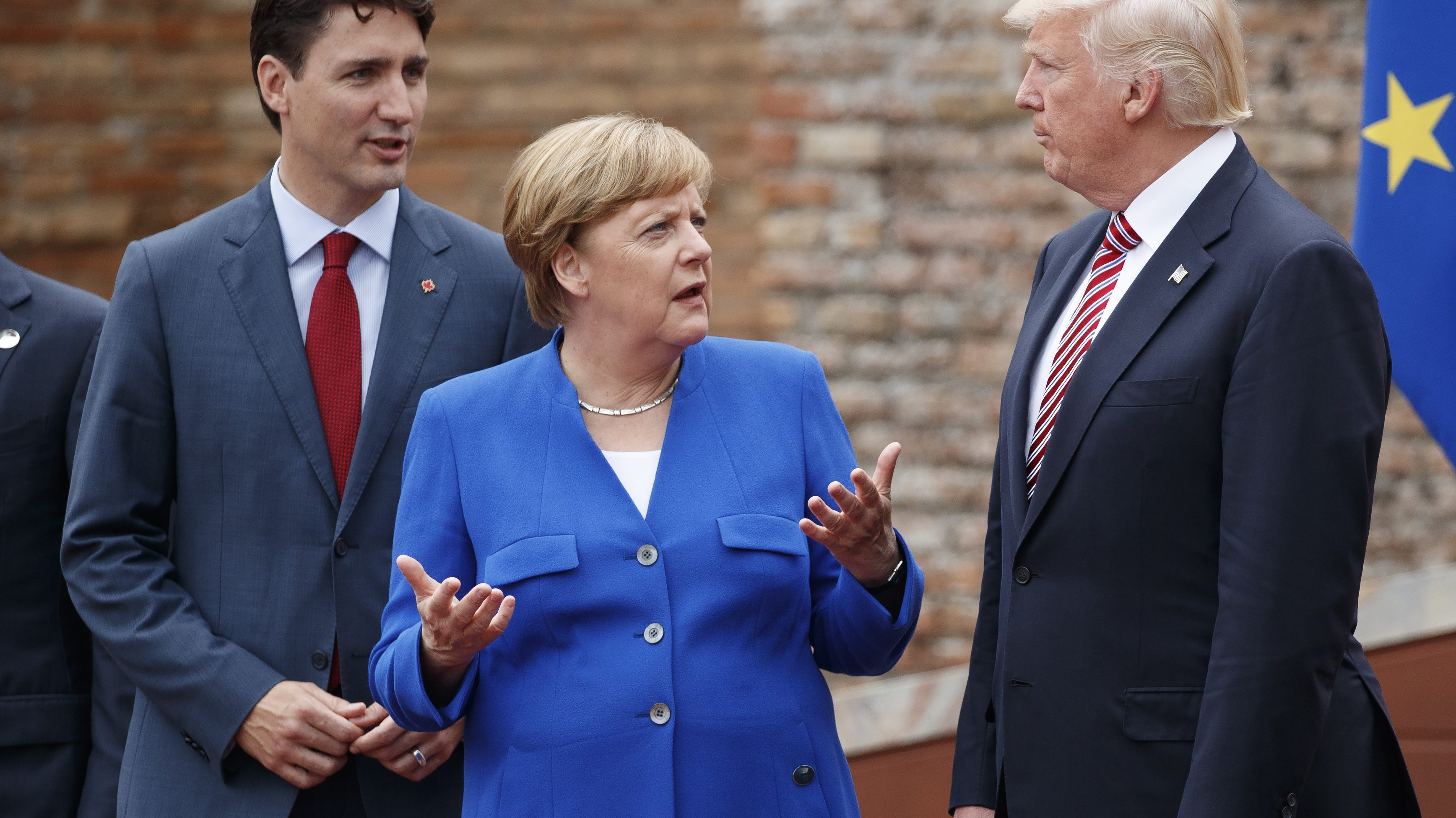 German Chancellor Angela Merkel, center, talks with Canadian Prime Minister Justin Trudeau, left, and President Donald Trump during a family photo with G7 leaders at the Ancient Greek Theater of Taormina during the G7 Summit, Friday, May 26, 2017, in Taormina, Italy. (AP Photo/Evan Vucci)
