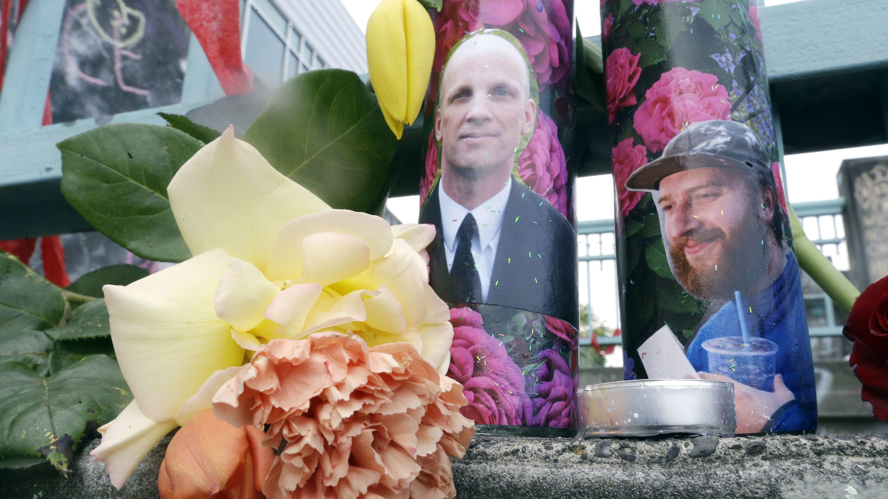 Candles with photos of Taliesin Namkai-Meche, right, and Ricky Best on them are shown at a memorial for the two men in Portland, Ore., Wednesday, May 31, 2017, The man charged with fatally stabbing the two men and injuring a third who tried to shield young women from an anti-Muslim tirade, appeared to brag about the attacks as he sat in the back of a police patrol car according to court documents.
