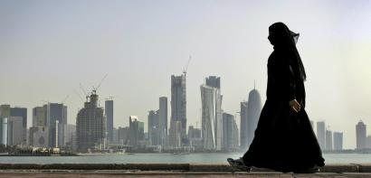 FILE - In this May 14, 2010 file photo, a Qatari woman walks in front of the city skyline in Doha, Qatar. Saudi Arabia and three Arab countries severed ties to Qatar on Monday, June 5, 2017 and moved to cut off land, sea and air routes to the energy-rich nation that is home to a major U.S. military base, accusing it of supporting regional terror groups.