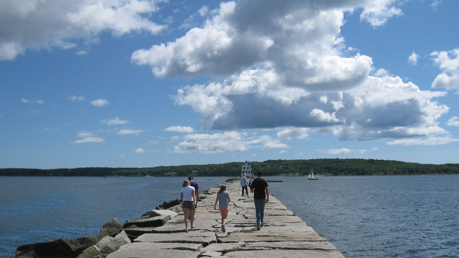 This Aug. 18, 2014, file photo, shows people walking on the Rockland Breakwater, a man-made granite jetty that stretches nearly a mile into Penobscot Bay from Rockland, Maine. A stroll on the jetty to the lighthouse at the other end almost feels like you're walking on water. As a summer vacation destination, Maine has something for everyone, from hiking and beaches to adventure and the arts.