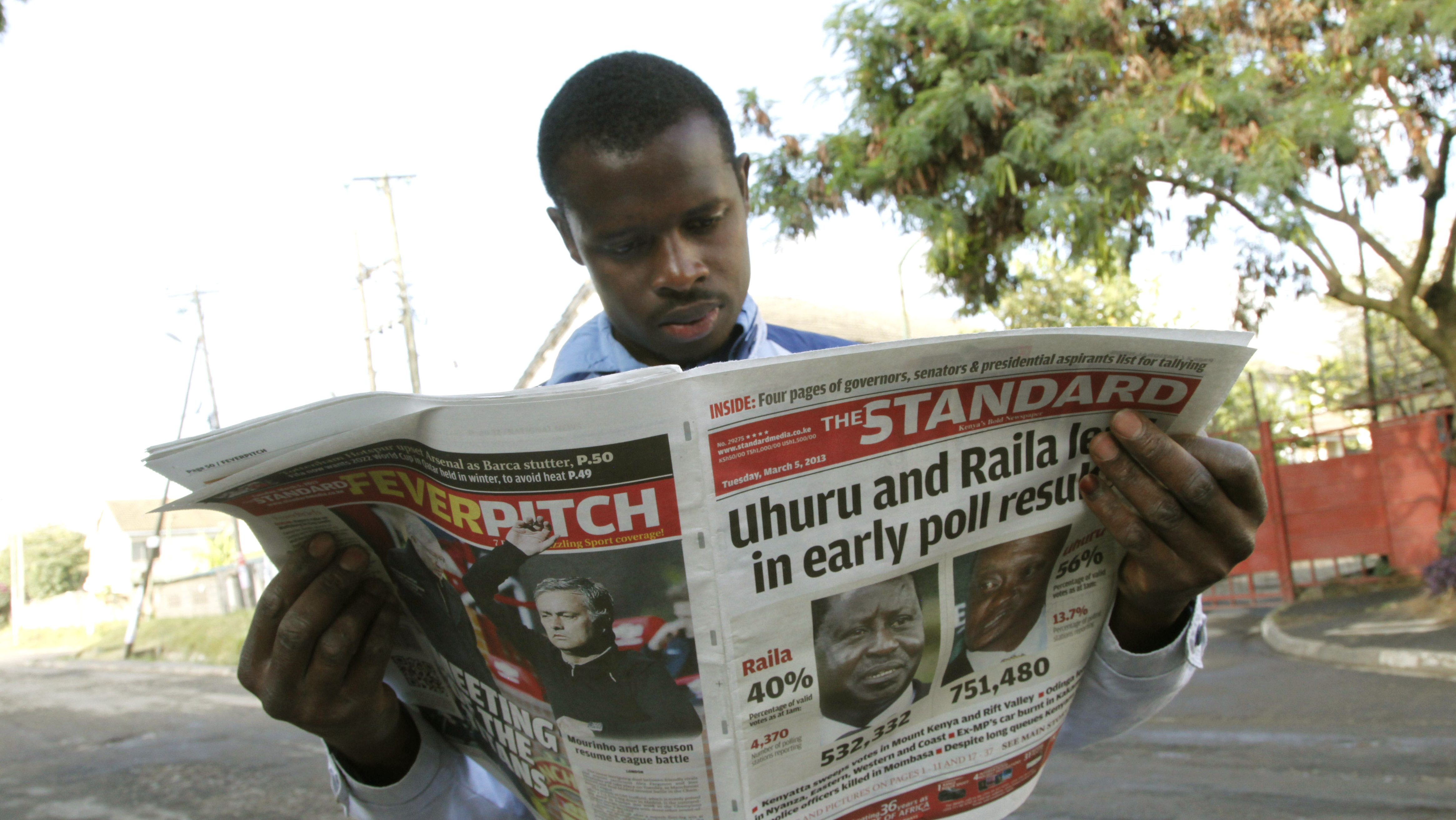 A Kenyan looks at a newspaper a day after the country's presidential election, at a roadside stall in Nairobi, Kenya Tuesday, March 5, 2013. Kenya's presidential election drew millions of eager voters who endured long lines to cast ballots Monday, but the vote was marred by violence that left 19 people dead, including four policemen hacked to death by machete-wielding separatists.