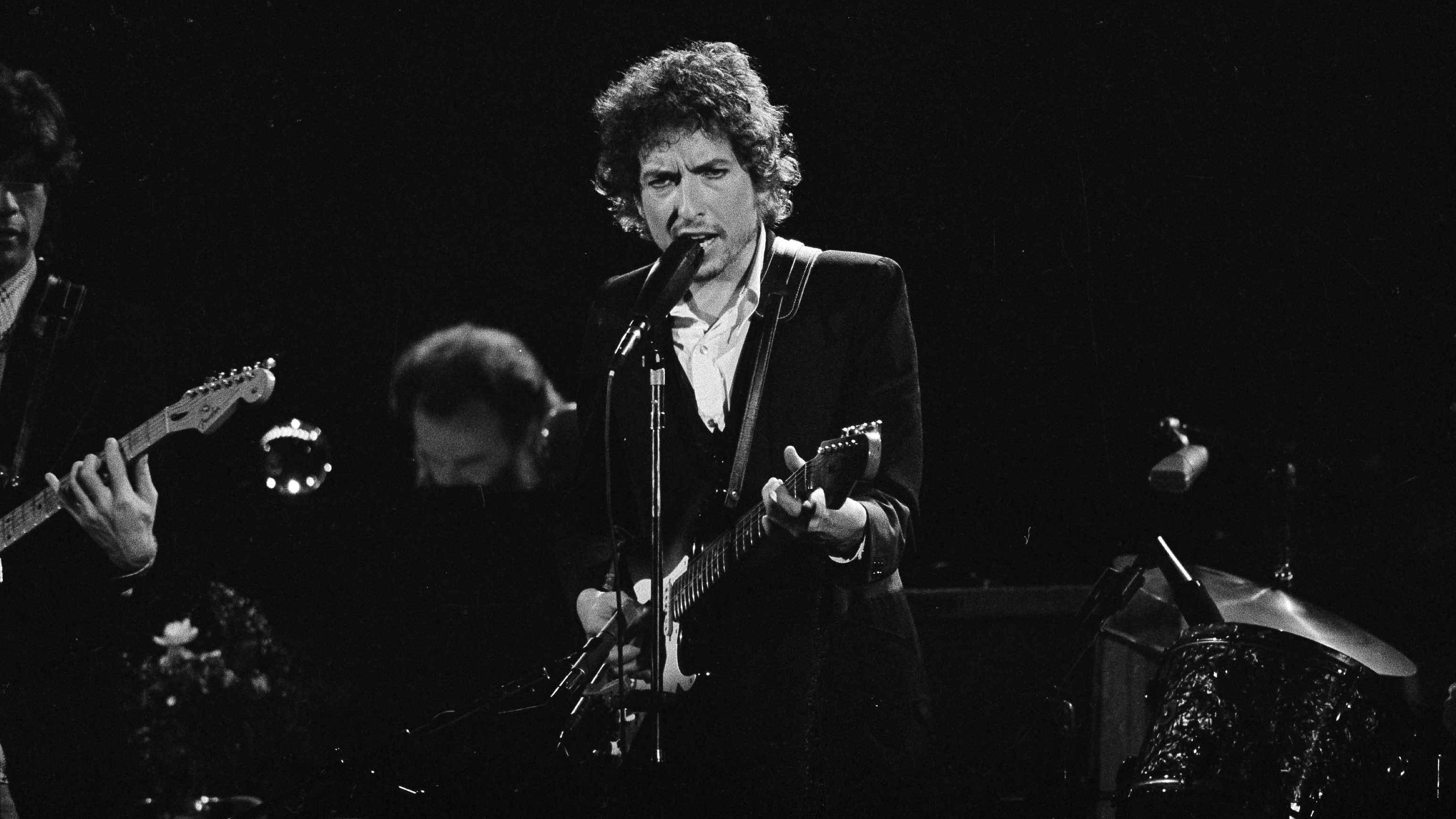 Musician Bob Dylan belts out a tune as members of The Band, Robbie Robertson, partially hidden left, and Garth Hudson, background center, accompany him during a concert at the Forum in Los Angeles, Calif., Feb. 15, 1974. The concert concluded a 21-city tour that began in Chicago, Ill., Jan. 3. (AP Photo/Jeff Robbins)
