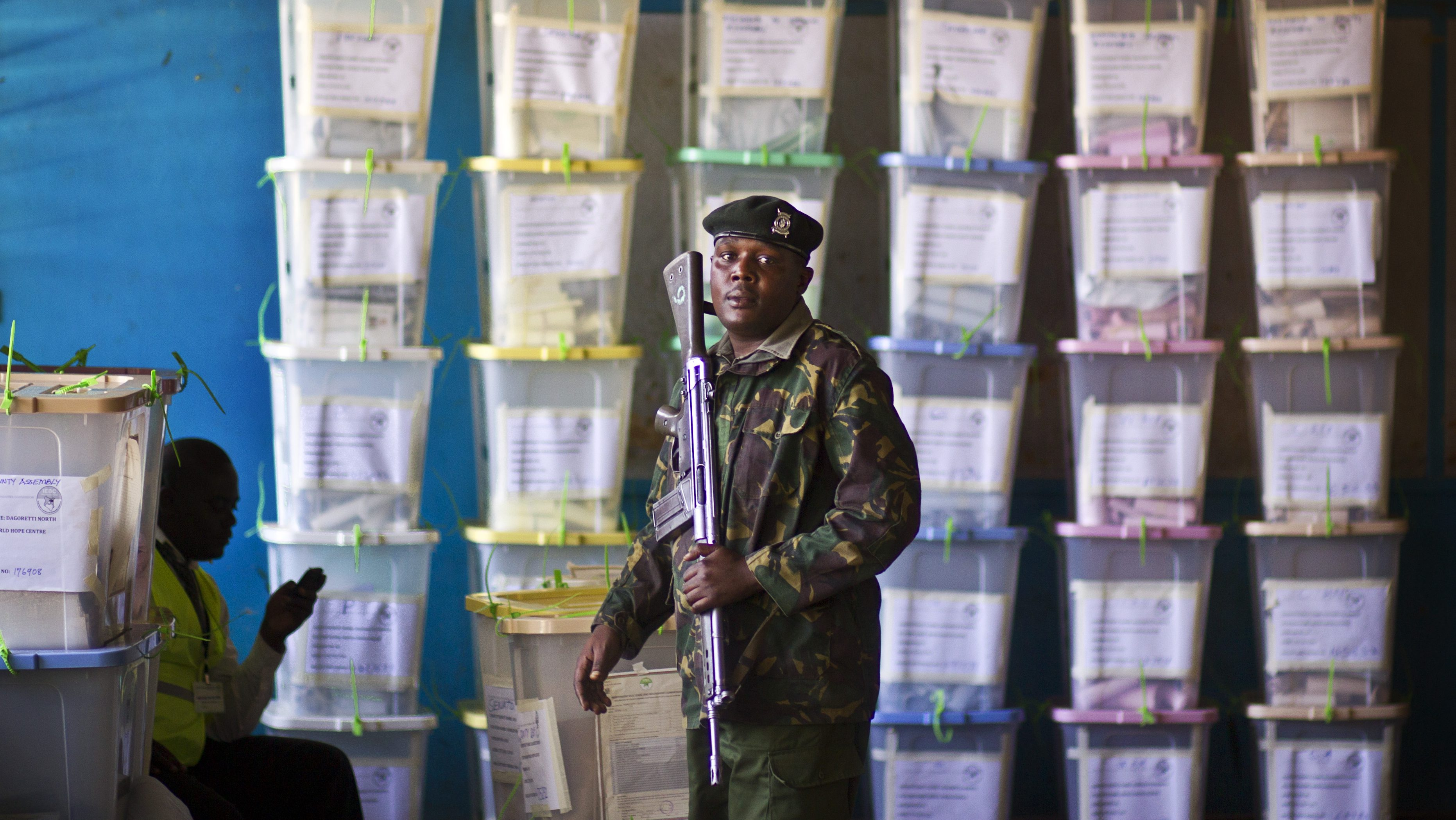 An officer of the prisons service helps to carry ballot boxes for stacking after their results were tallied, at a vote tallying center in Nairobi, Kenya Tuesday, March 5, 2013. With about a third of ballots counted provisional results showed Deputy Prime Minister Uhuru Kenyatta, who faces charges at the International Criminal Court, taking an early lead Tuesday as votes were counted the day after the country's presidential election.