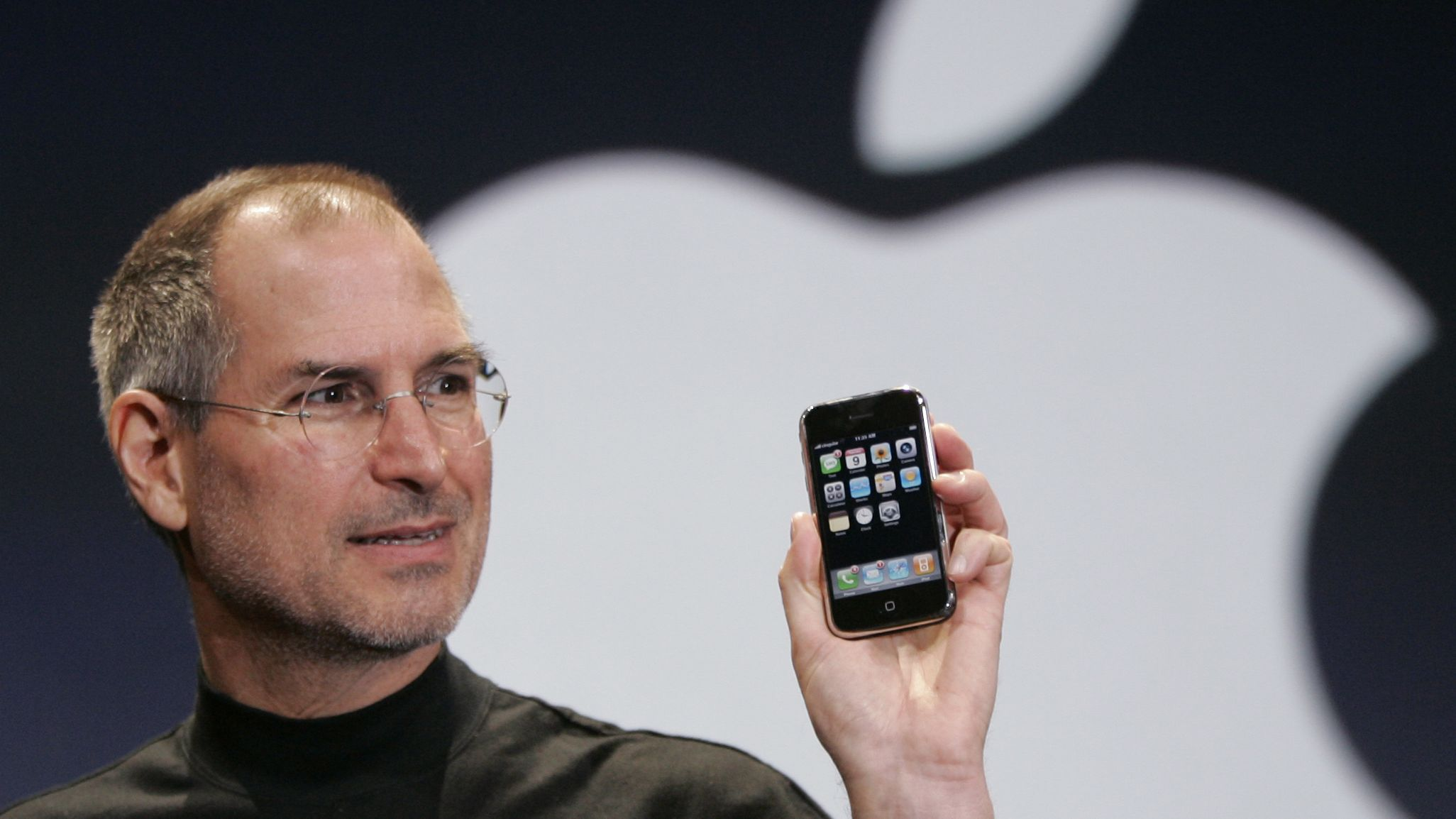In this Jan. 9, 2007 file photo, Apple CEO Steve Jobs holds up an Apple iPhone at the MacWorld Conference in San Francisco. Apple Inc. on Wednesday, Aug. 24, 2011 said Jobs is resigning as CEO, effective immediately. He will be replaced by Tim Cook, who was the company's chief operating officer. It said Jobs has been elected as Apple's chairman.
