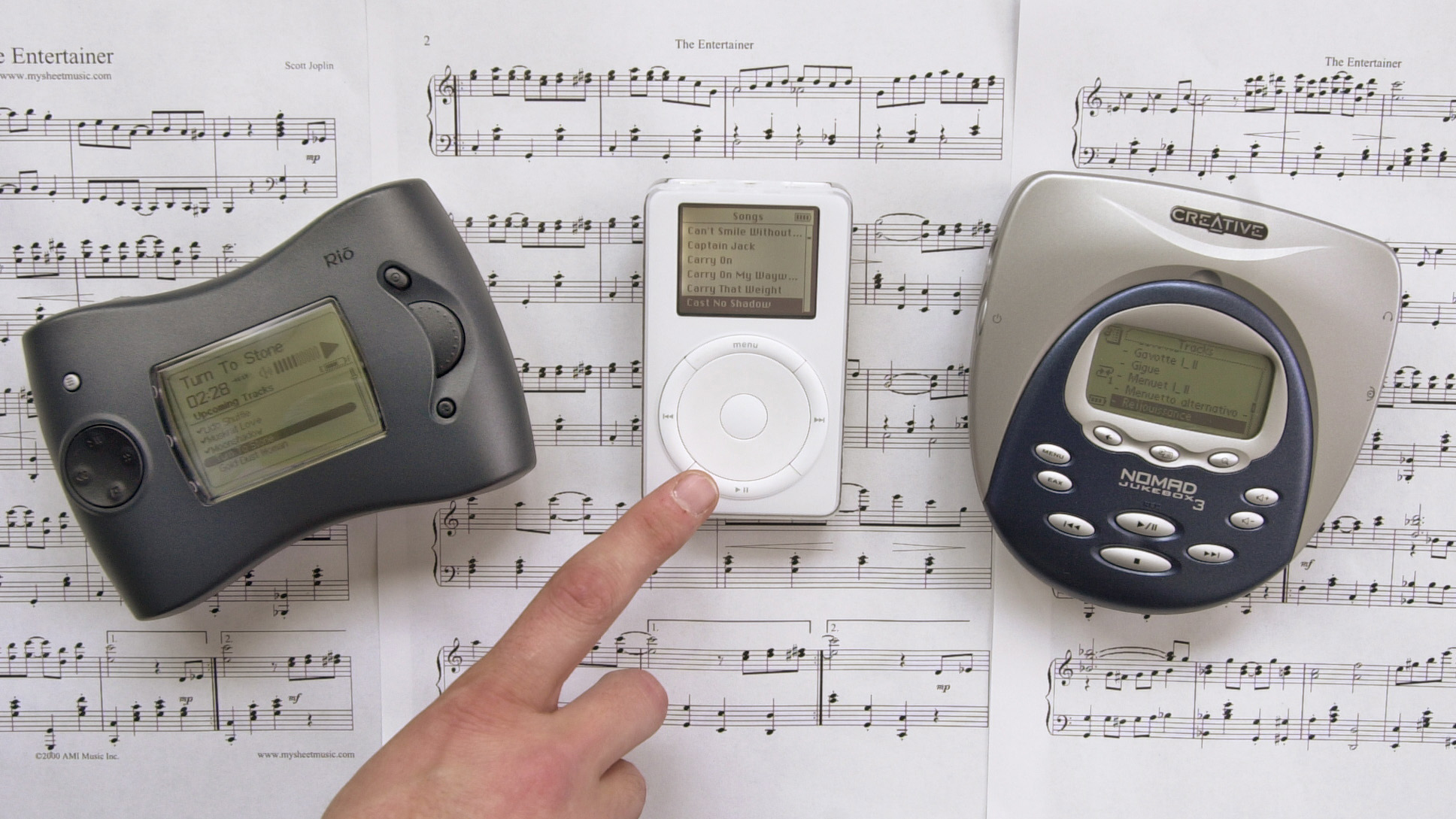 "Three digital music players; from left, SonicBlue's RioRiot, Apple Computer's iPod and Creative Labs' Nomad Jukebox 3, are displayed on the sheet music for ""The Entertainer"" in San Jose, Calif., Thursday, April 11, 2002.  The three new digital music players  store thousands of songs on built-in hard drives and run for 11 hours on a single charge.  (AP Photo/Paul Sakuma)"