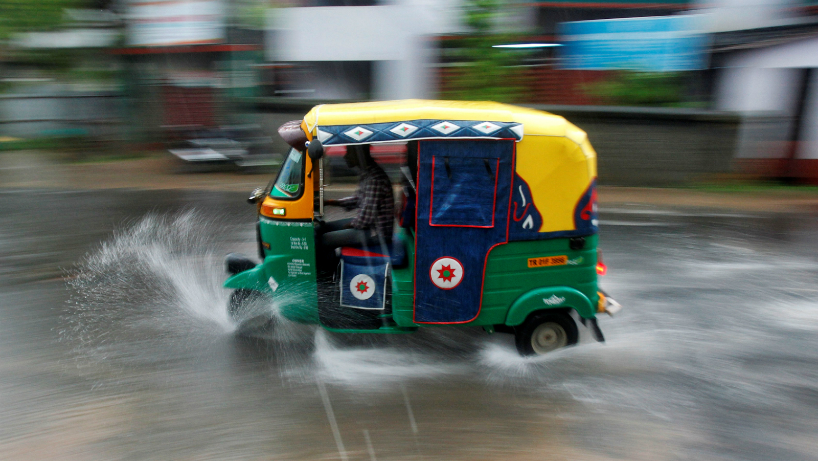 A person drives an auto rickshaw through heavy rains in Agartala, India June 1, 2017.