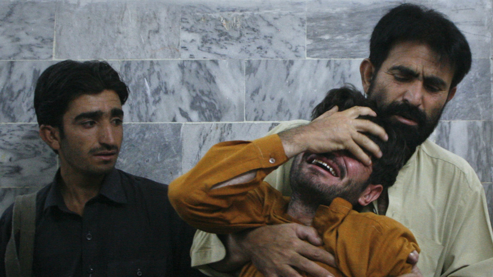 A man is comforted by his relative after he arrived at the local hospital in Quetta, September 7, 2012, to find a family member shot dead. Unidentified gunmen on motorbike on Friday shot dead a senior police officer, investigating sectarian killings in Pakistan's troubled southwestern province of Balochistan, police said.