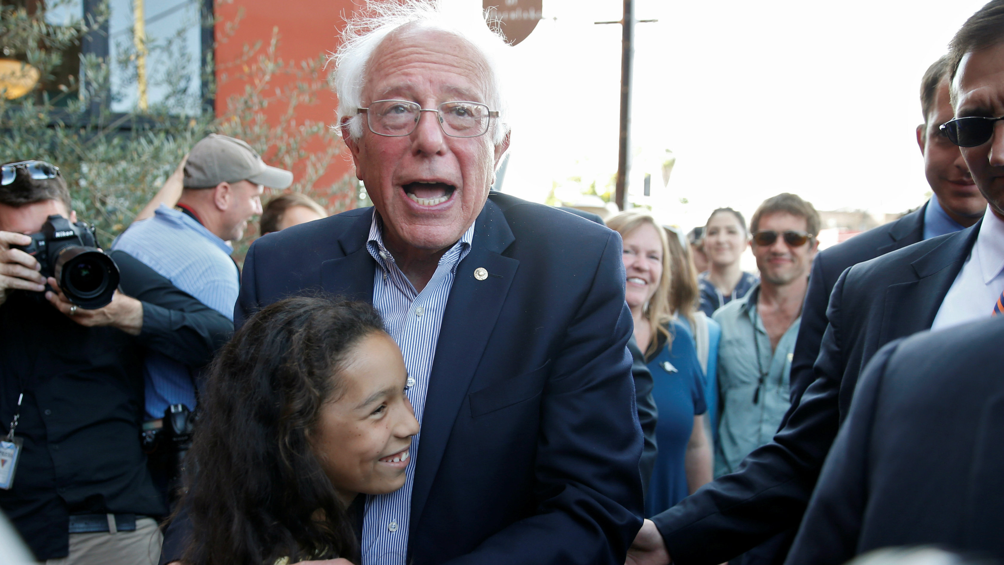 Bernie Sanders hugging a child.