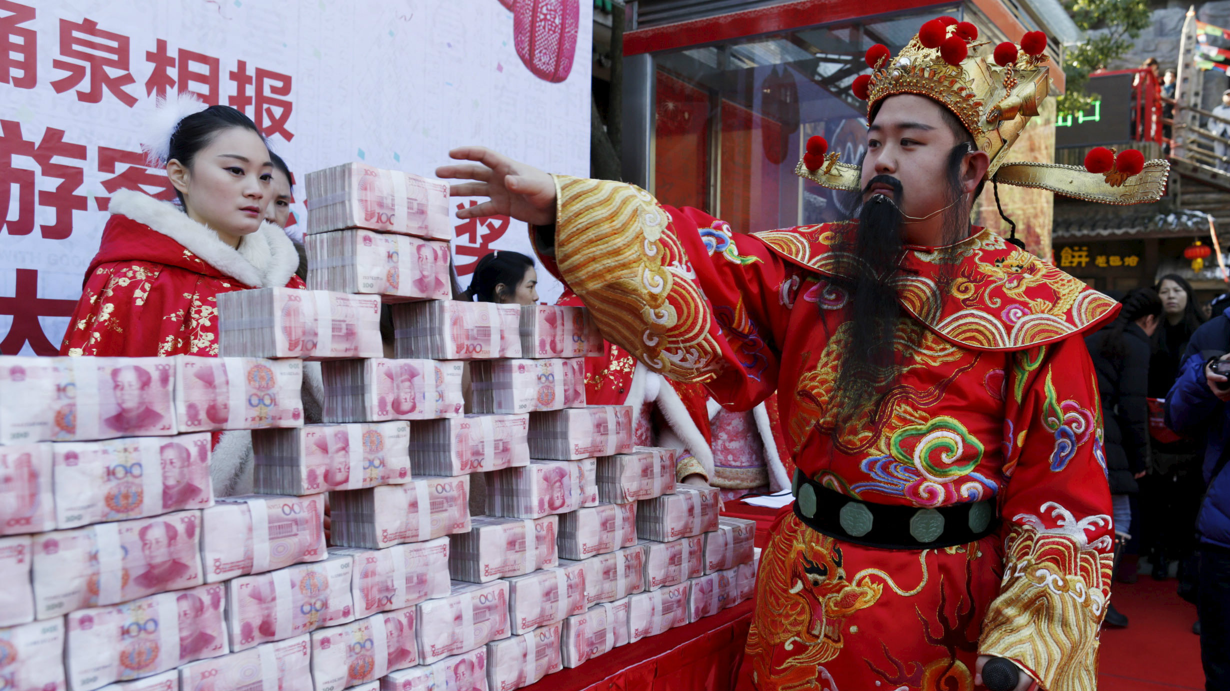 A man dressed as Chinese God of Fortune tries to reach a bundle of 100-yuan banknotes during an event held to celebrate the upcoming Spring Festival, at a park in Hangzhou, Zhejiang province, China January 26, 2016. The event offered 5 million yuan ($760,000) for 10 visitors to snatch inside a glass cage with an air blower on. The visitors were allowed to take away all the money they could grab with their hands within one minute. One of the visitors won 18,300 yuan ($2,800) from the game, according to local media.
