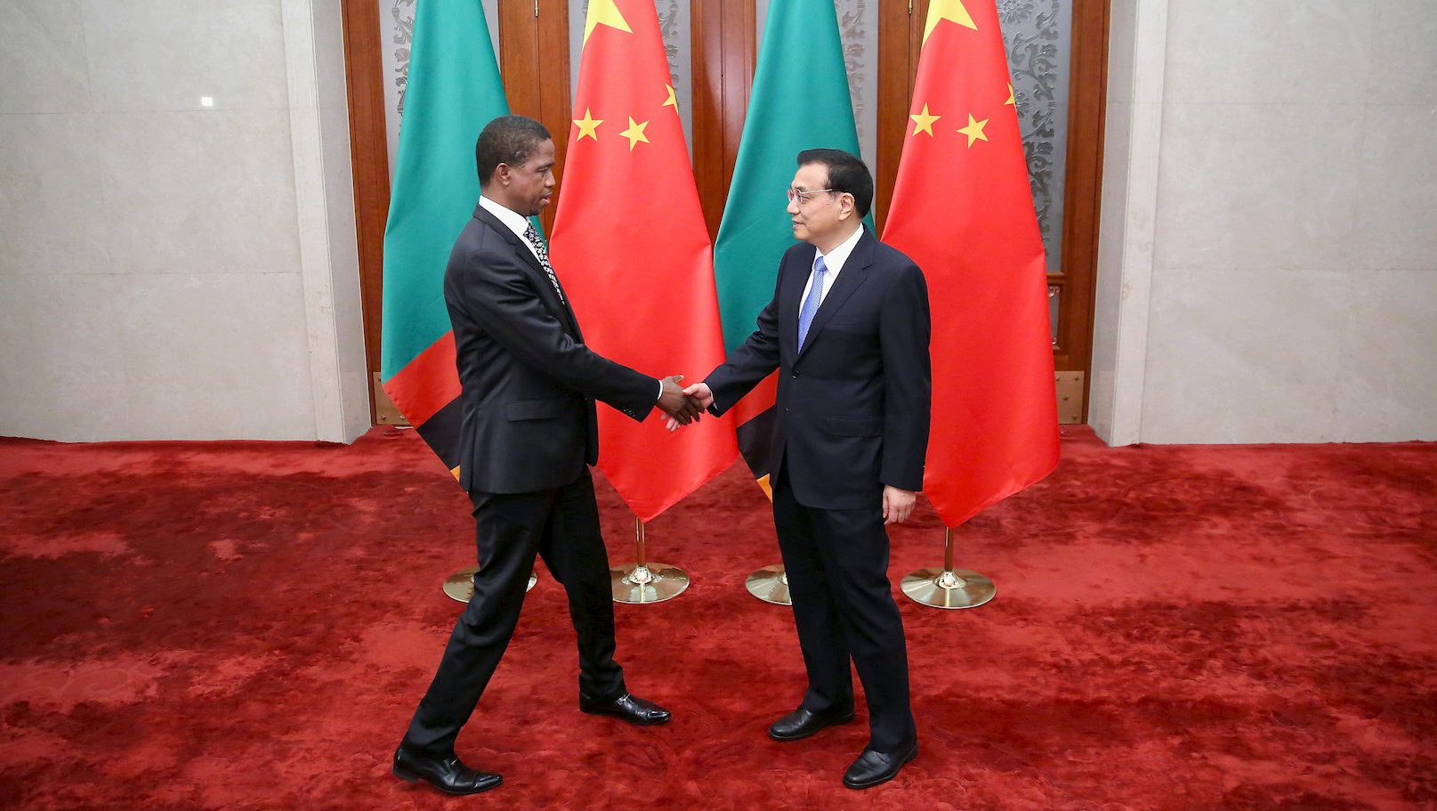 Chinese Premier Li Keqiang (R) shakes hands with Zambia's President Edgar Chagwa Lungu at the Great Hall of the People in Beijing March 30, 2015.