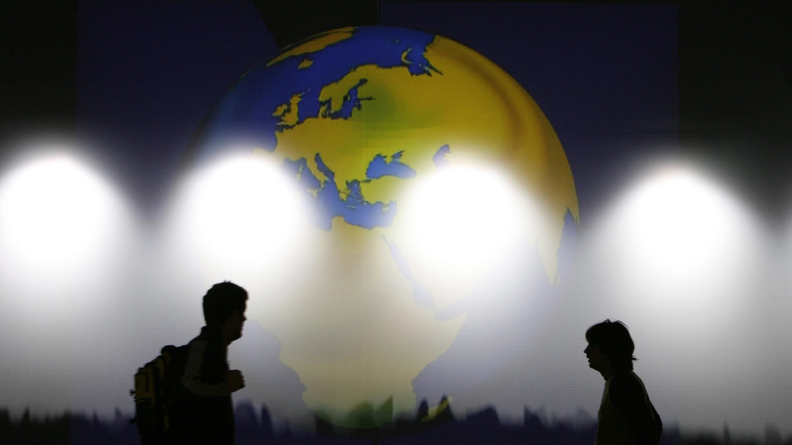 Volunteers walk in front of a projection of the globe as they prepare the main stage for the WEF in the Swiss Alpine resort town of Davos