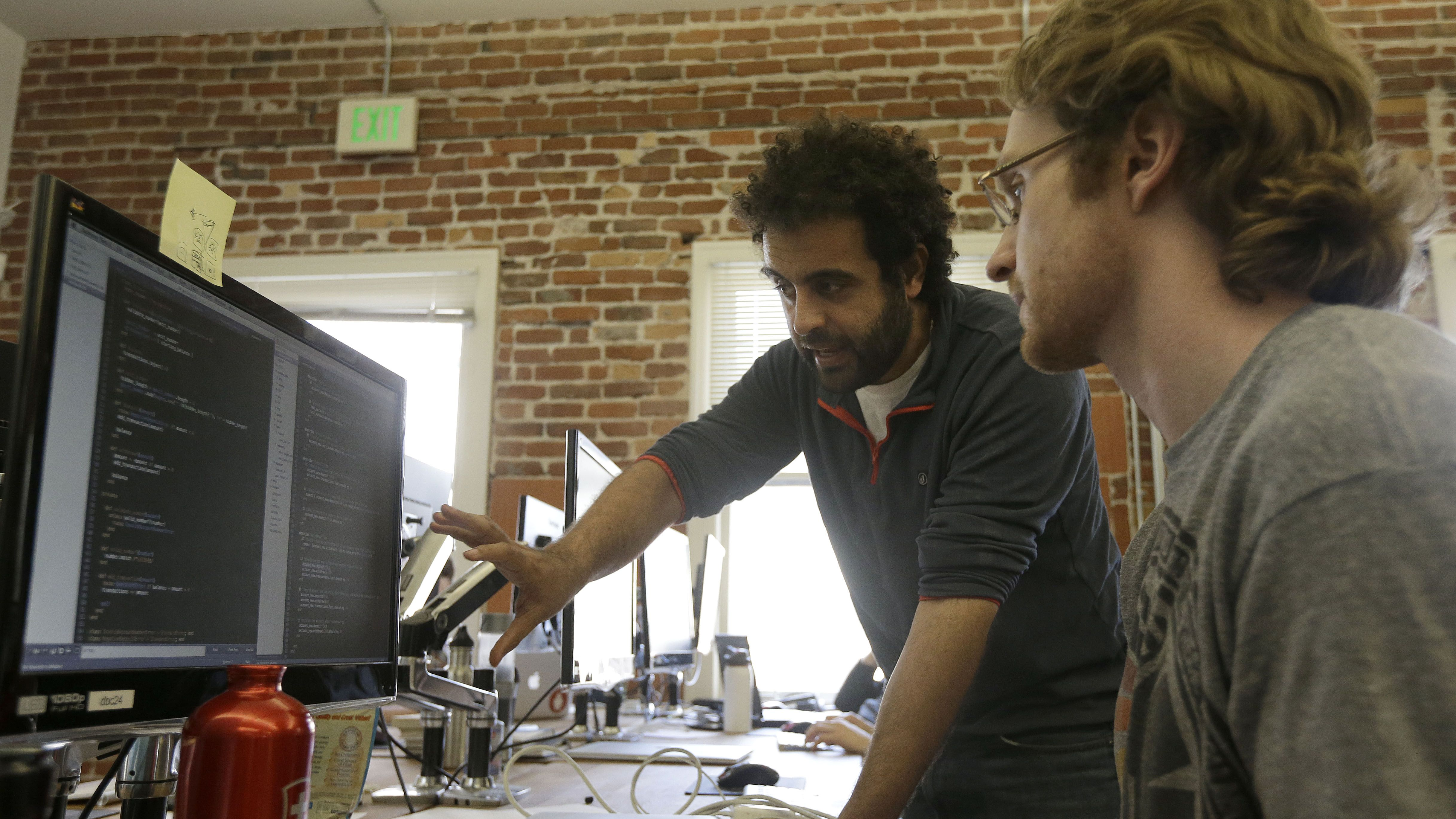 "Shereef Bishay, co-founder of Dev Bootcamp, center, talks with student Ryan Guerrettaz during a class at Dev Bootcamp in San Francisco, Tuesday, April 2, 2013. Dev Bootcamp is one of a new breed of computer-programming schools that's proliferating in San Francisco and other U.S. tech hubs. These ""hacker boot camps"" promise to teach students how to write code in two or three months and help them get hired as web developers, with starting salaries between $80,000 and $100,000, often within days or weeks of graduation. (AP Photo/Jeff Chiu)"