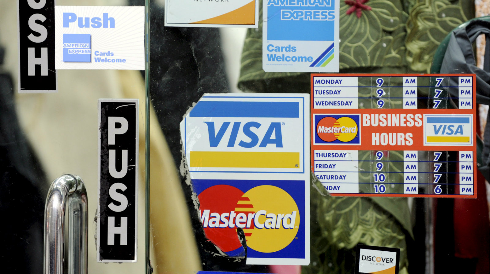 Stickers show the credit cards accepted at a store in New York, New York, USA, on 22 October 2008. With the United States economy faltering, consumers are likely to have a much more difficult time obtaining credit for purchases.  Credit