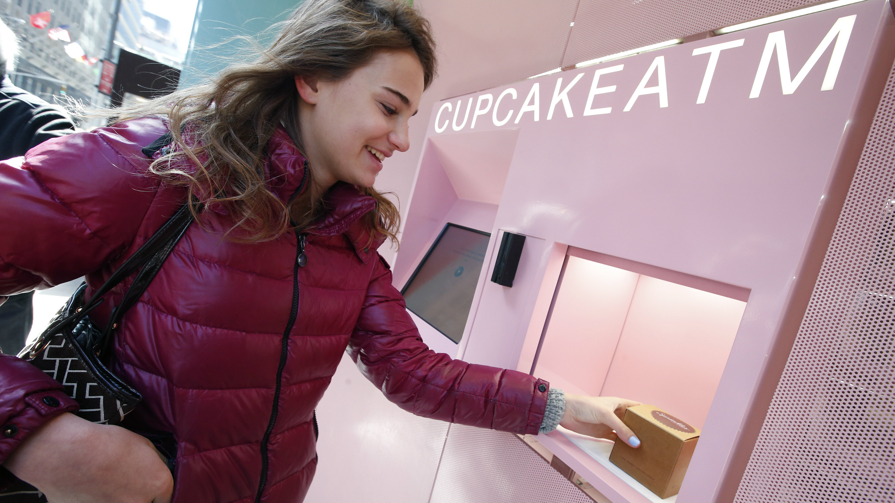 A woman takes a chocolate marshmallow cupcake from the Cupcake ATM at Sprinkles Cupcake Bakery in New York City's Upper East Side in Manhattan March 26, 2014. A 24-hour sidewalk cupcake-dispensing machine which opened on Tuesday where purchases are made by credit card, Sprinkles' Cupcake ATM is New York City's first and joins the Beverly Hills-based company's ATMs already opened in Los Angeles, Atlanta, Chicago and Dallas.
