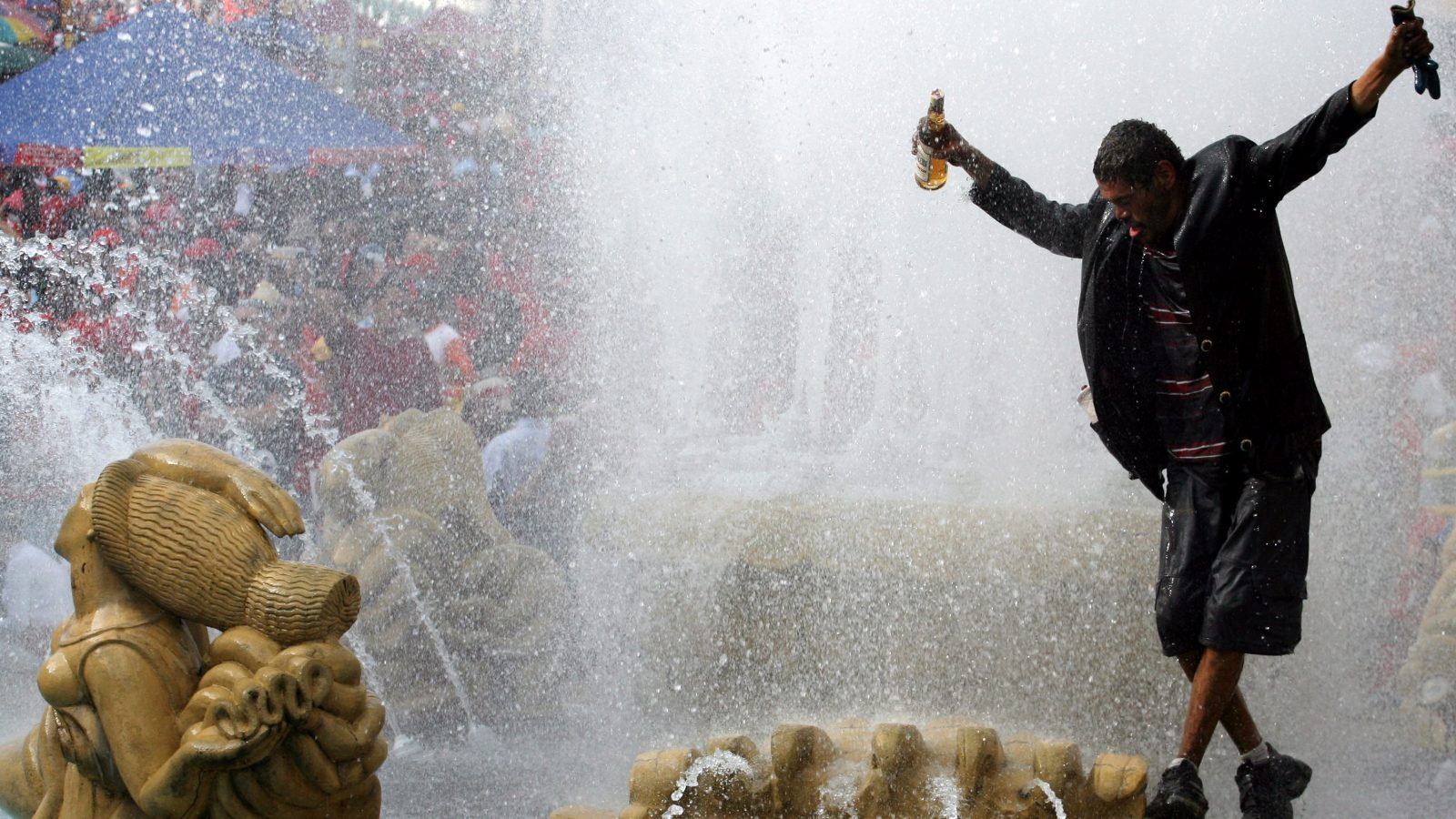A drunk man plays in a fountain during President Hugo Chavez's campaign rally in Caracas September 1, 2006. REUTERS/Jorge Silva   (VENEZUELA) - RTR1GWOW