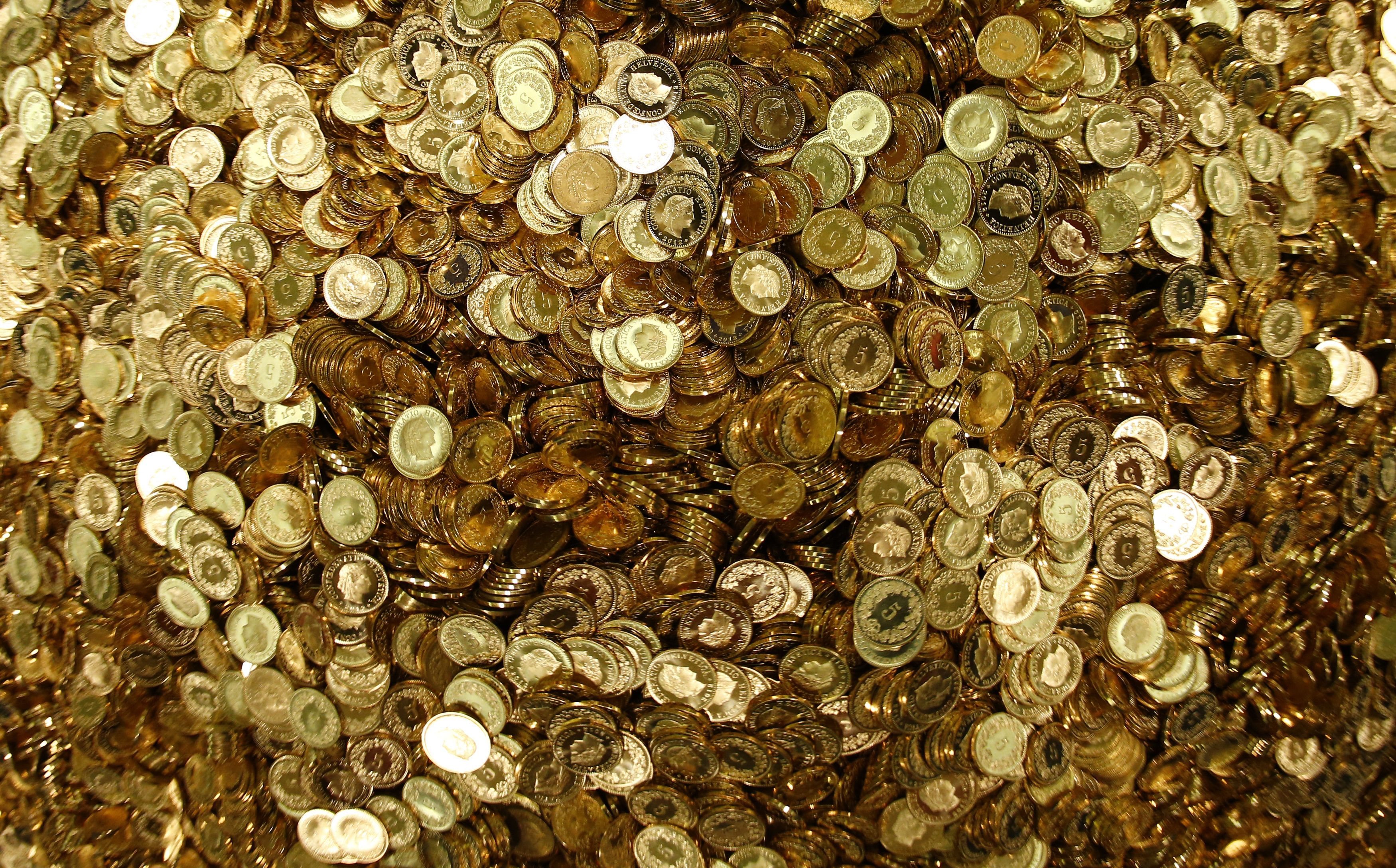 """Swiss Francs five cent coins are heaped in a pile as members for the initiative """"CHF 2,500 monthly for everyone"""" (grundeinkommen) open rolls of five cent coins in the old vault of the former Schweizerische Volksbank in Basel October 1, 2013. The committee dumped 8,000,000 five cent coins, weighting 15 tones, over the Federal Square in Bern on Friday, before delivering 126,000 signatures to the Chancellery to propose a change in the constitution to implement their initiative. The initiative aims to have a minimum monthly disposal household income of CHF 2,500 (US$ 2,700) given by the government to every citizen living in Switzerland.    Picture taken October 1, 2013."""