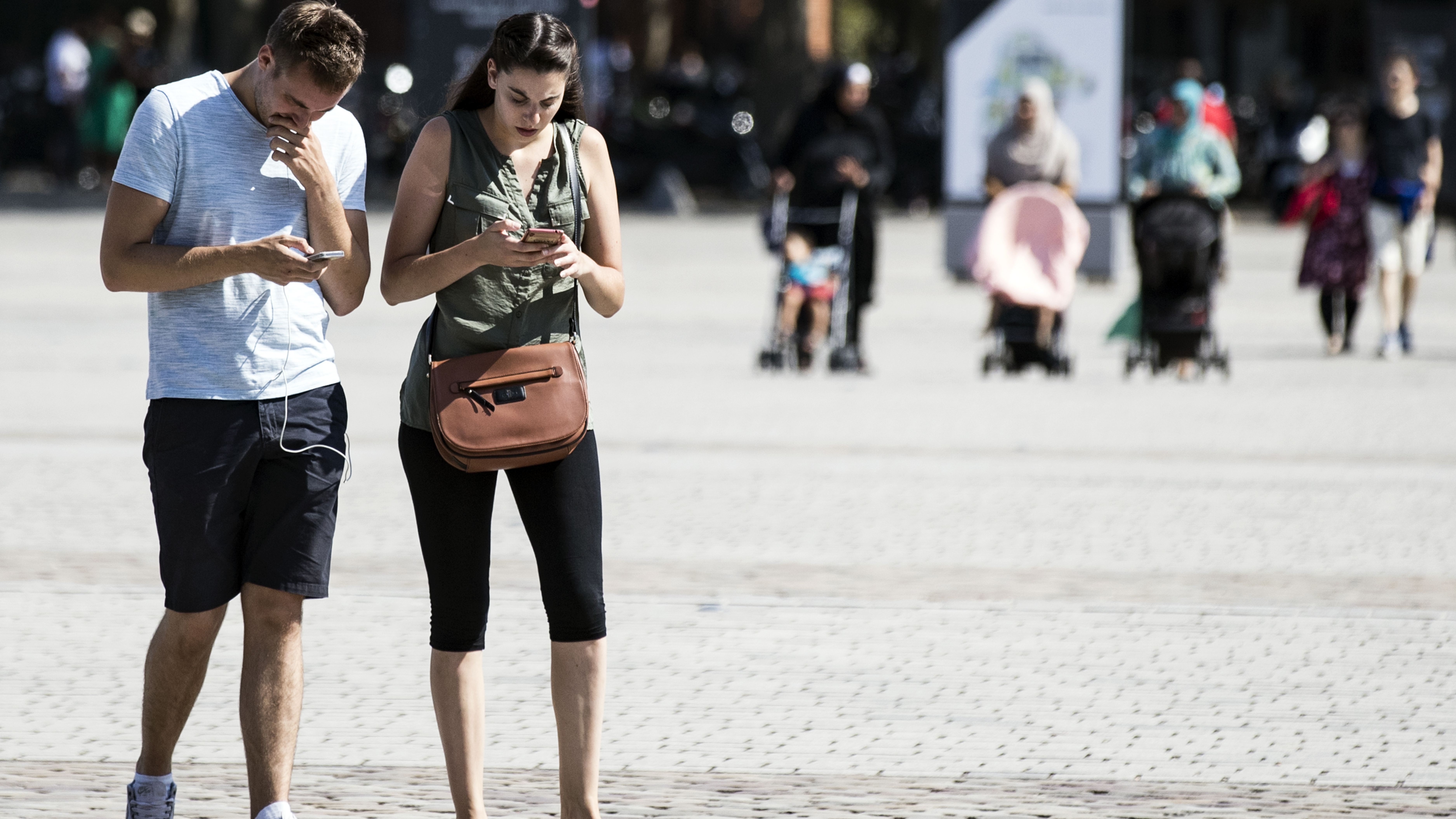 epa05487399 A couple searches for Pokemons on their phones at the Parc de la Villette where some rare creatures from the game are known to appear in Paris, France, 15 August 2016. Launched at the beginning of July by the US company Niantic, the mobile phone game 'Pokemon Go' has found a real success worldwide and already have generated more than 160 US million dollars.  EPA/ETIENNE LAURENT