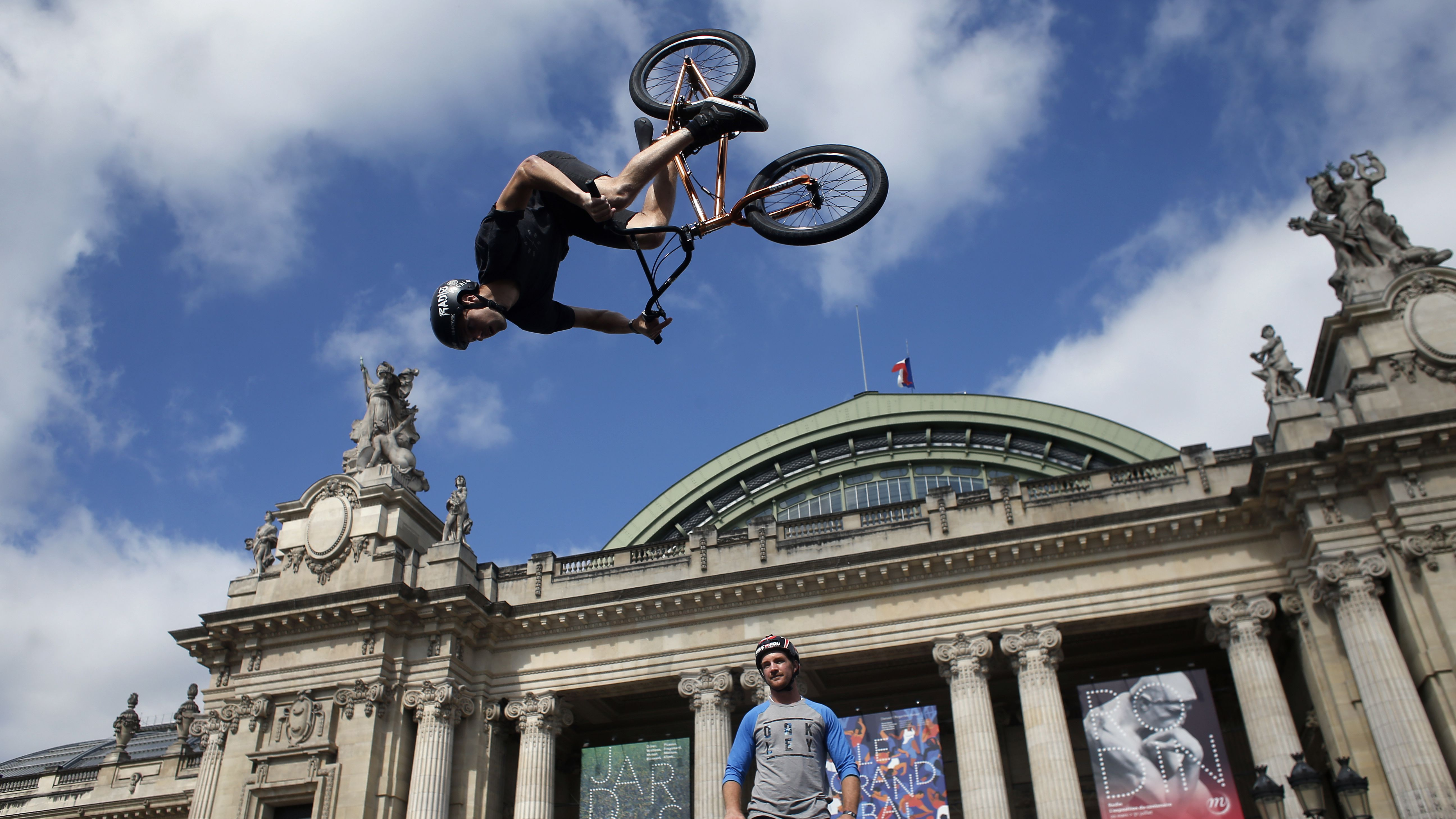Belgian biker Kenneth Tancre performs outside the Grand Palais museum in Paris, Friday, June 23, 2017. Paris is aiming to boost its bid for the 2024 Olympics by turning some of its world-famous landmarks over to sports for two days, with 100-meter races on a track floating on the Seine, high-diving into the river, cycling around the Arc de Triomphe and other events to showcase the French capital's suitability for the games.