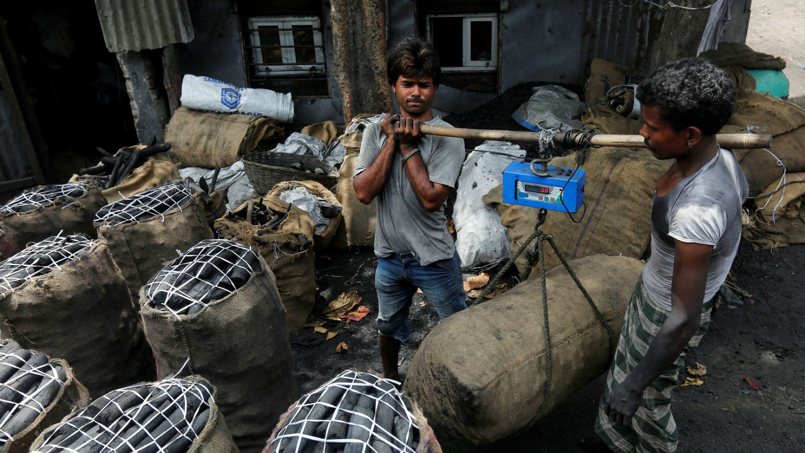Workers weigh a bag of coal outside a warehouse in an industrial area in Mumbai, India May 31, 2017.