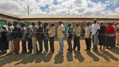 People wait in line to vote outside of a polling station in Munyu, in Rift Valley Province, some 75 km north of capital Nairobi, Kenya, 04 August 2010. The government is stepping up the security, especially in volatile Rift Valley Province, scene of the worst fighting in 2007-08 post-election violence and home to many who plan to disapprove the new draft constitution, to ensure that the country does not repeat the bloodshed that left some 1,300 dead in 2007. A survey shows more than 65 per cent of registered voters will vote in favor of the new constitution, while 25 per cent will reject it. Some 12 million Kenyans across the nation are voting in a referendum on the proposed laws, which would curve the powers of the president and devolves more power to local governments. The official result is expected to be announced by 05 August.