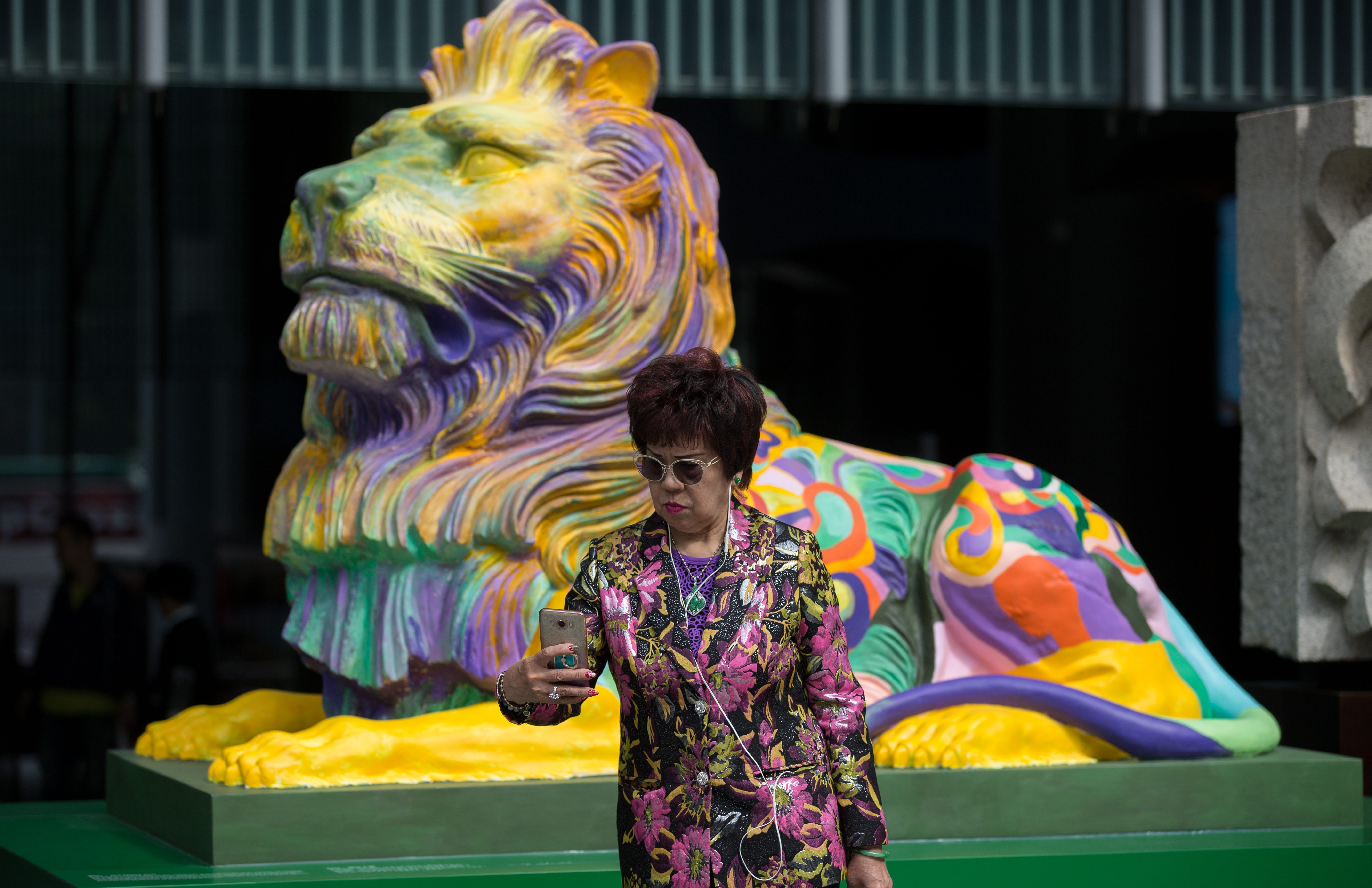 A woman takes a selfie next to a replica of the HSBC lion painted in rainbow colours and displayed outside the bank's headquarters in Hong Kong, China, 06 December 2016. Several groups of activist including The Family School SODO Concern Group, Parents for the Family Association, Overturning LGBT Agenda and Next Generation Orientation have launched a joint online signature campaign expressing disapproval at the display. The groups claimed the rainbow lions have offended both HSBC customers and shareholders. The bank kicked off the 'Celebrate Pride, Celebrate Unity' campaign in November by displaying replicas of the bank's iconic lions in rainbow colours, created by a local LGBT artist, in front of its Hong Kong headquarters.