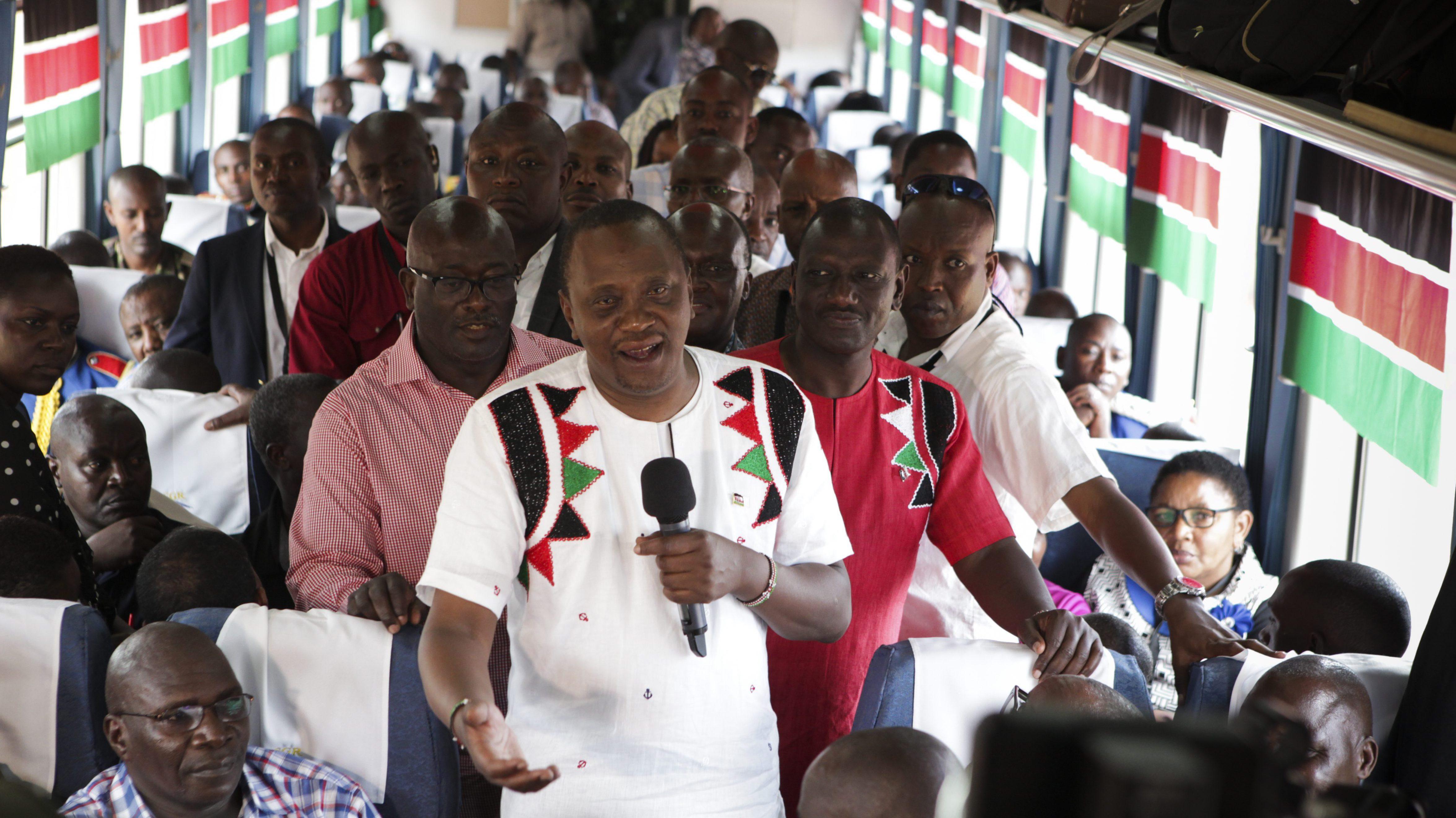 Kenyan president Uhuru Kenyatta, with his deputy president William Ruto, addresses a passenger train on the Standard Gauge Railway.