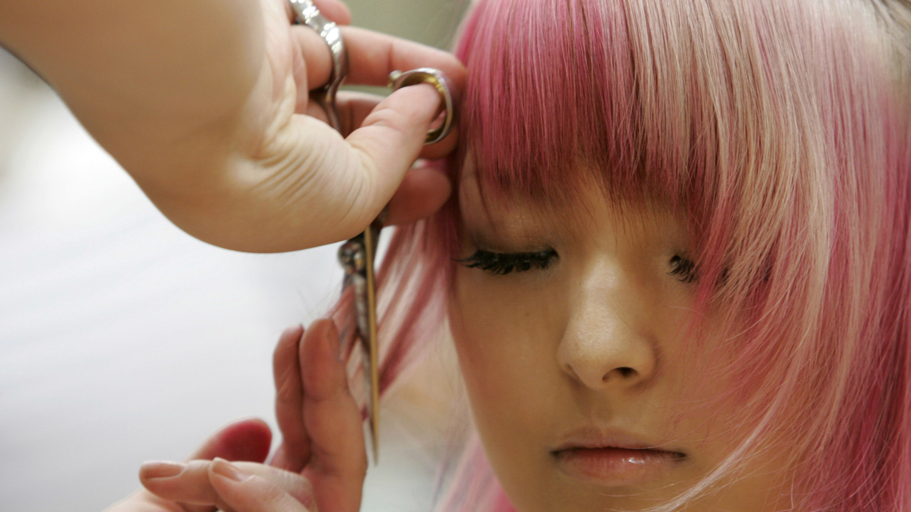 A stylist cuts a model's hair during the cut competition at the Nihon Hair Design Kyokai's hair contest in Tokyo July 10, 2007. 60 stylists competed in timed events to cut models' hair for a grand prize of 150,000 yen (US$1,200).