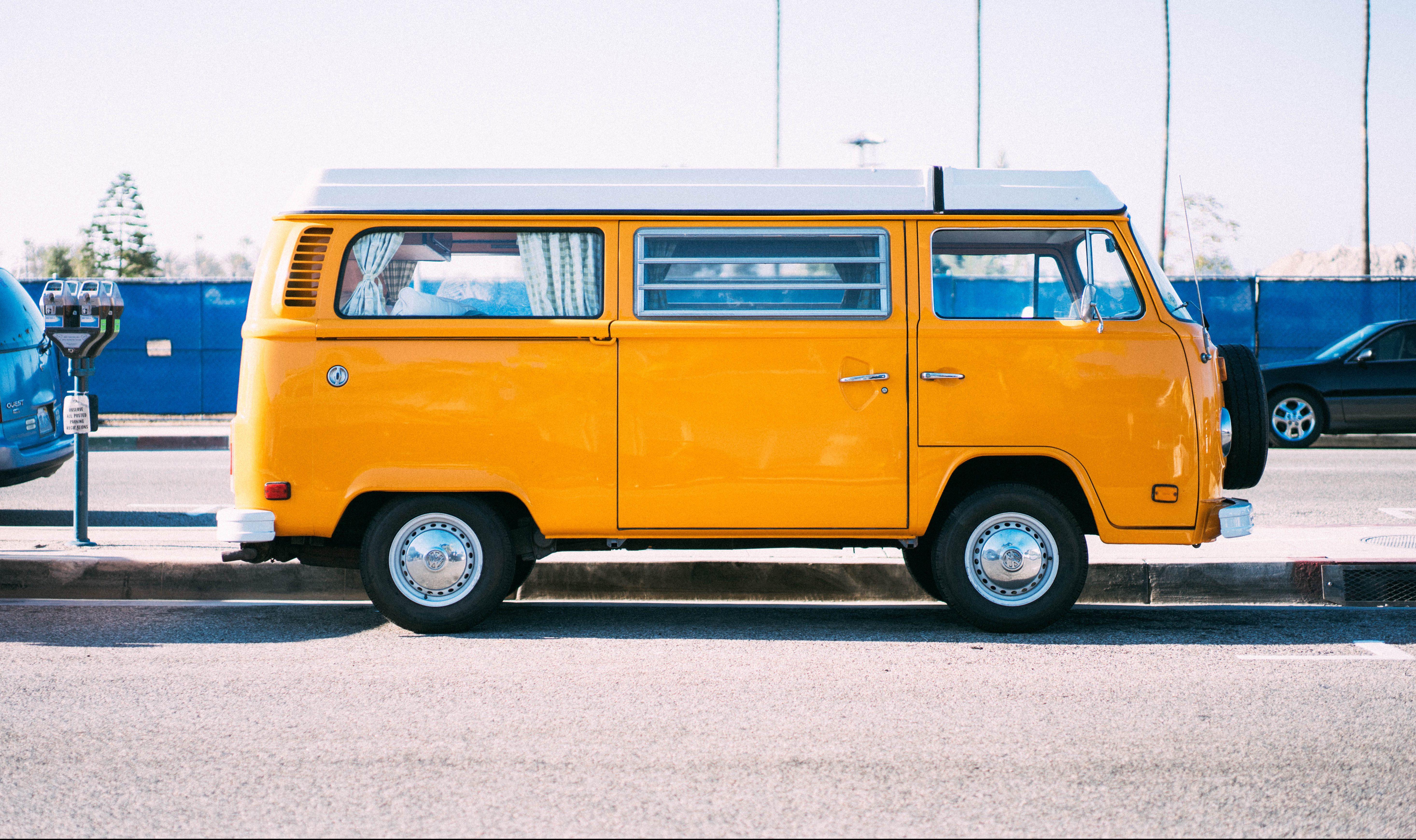 A yellow VW van on the sidewalk.