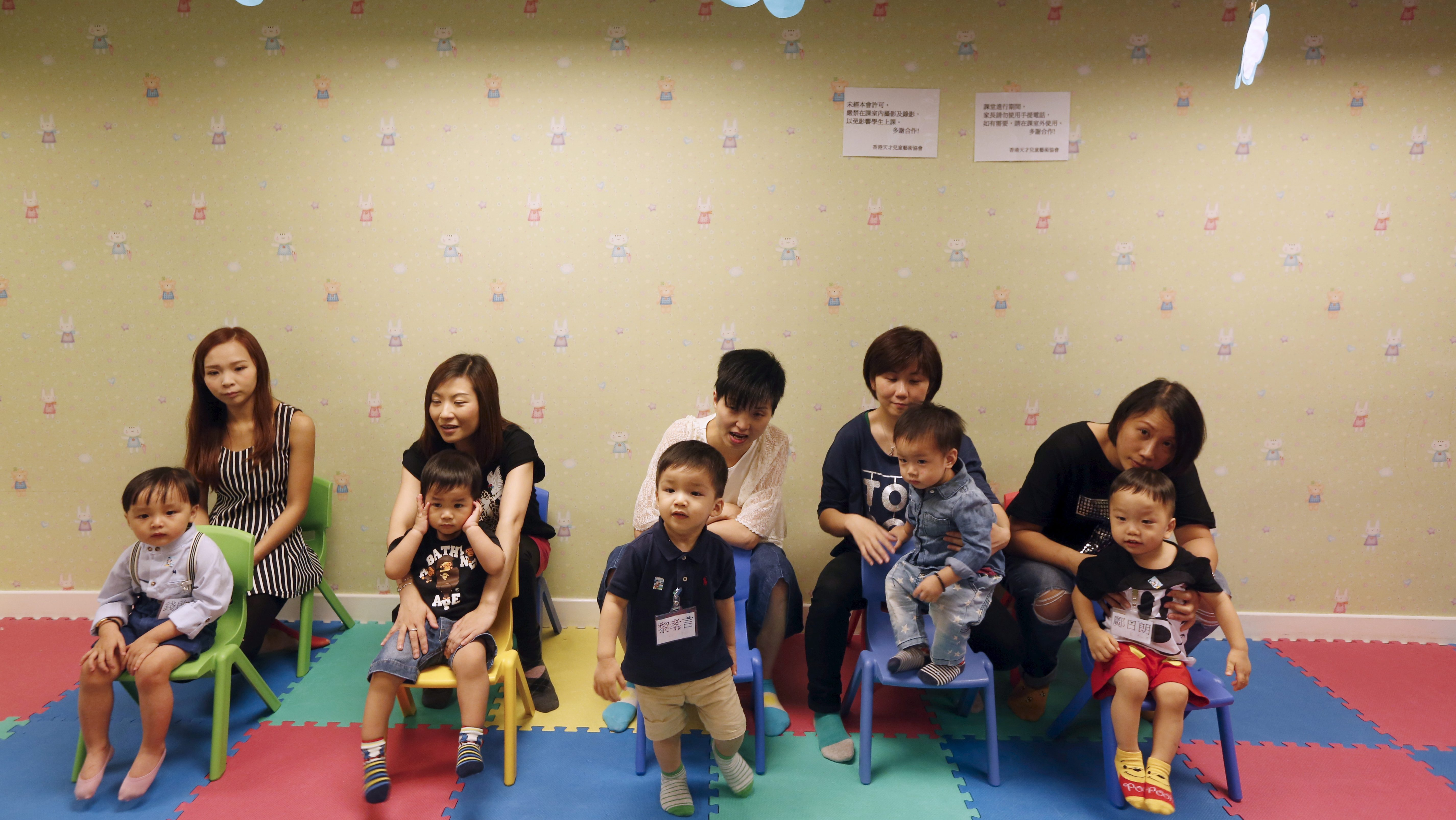 Mothers and their sons participate in a specialized class preparing toddlers for kindergarten interviews in Hong Kong, China May 17, 2015. Parents believe that getting a place in a good kindergarten will help them secure a spot in a good primary and secondary school and pave the way for a good start in life. With the competition being so fierce, sought-after kindergartens can be selective about who they let in. Pre-kindergarten interview courses train them to be disciplined, responsive and polite through games, music and dance. They also offer one-on-one mock interview sessions. Picture taken May 17, 2015. REUTERS/Bobby Yip - RTX1E7O9