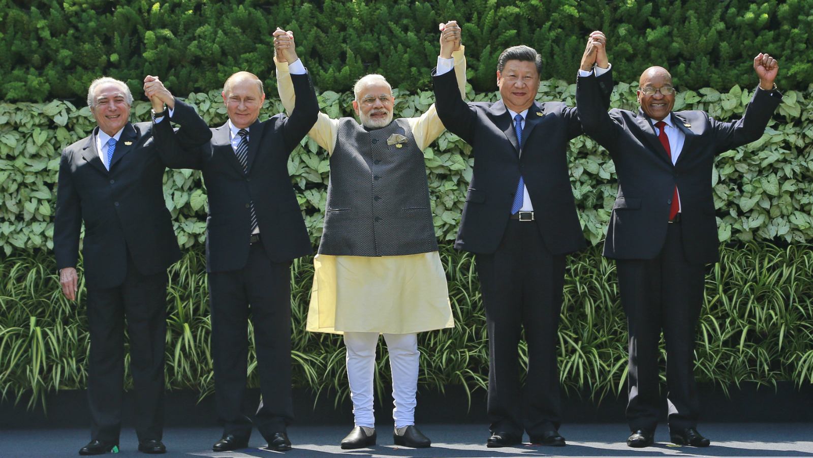Leaders of BRICS countries, from left, Brazilian President Michel Temer, Russian President Vladimir Putin, Indian Prime Minister Narendra Modi, Chinese President Xi Jinping, and South African President Jacob Zuma raise their hand for a group photo at the start of their Summit in Goa, India, Sunday, Oct. 16, 2016. Leaders of five of the world's fast-rising powers are meeting in the southwestern Indian state of Goa for their annual summit at a time when their ability to shape the global dialogue on international politics and finance is increasingly being questioned. Brazil, Russia, India, China and South Africa, or BRICS, face the tough task of asserting their growing influence as a power group even as they bridge their own trade rivalries to help grow their economies. (AP Photo/ Anupam Nath)