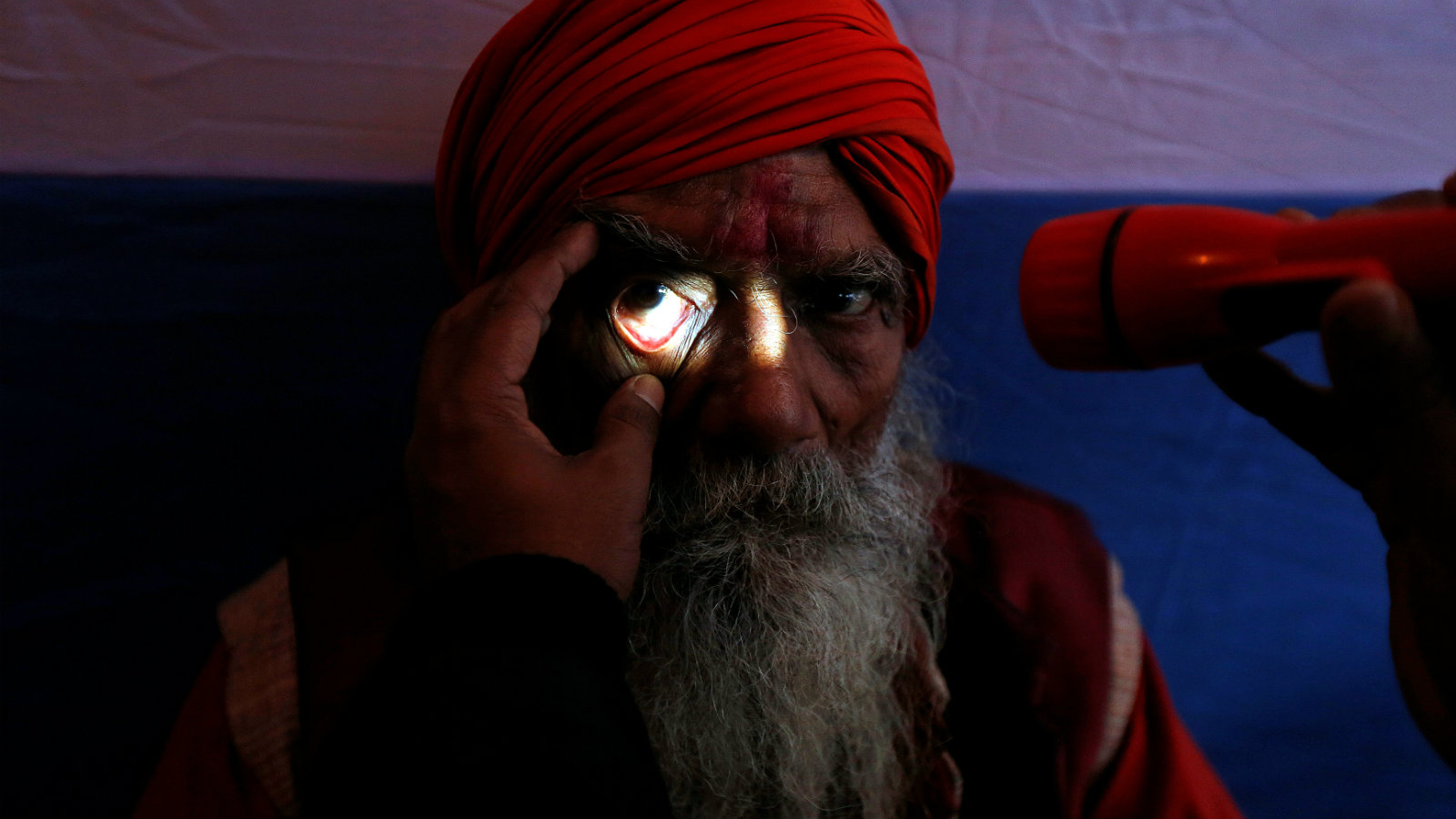 "A Sadhu or a Hindu holy man undergoes an eye examination at a free eye-care camp organised by social workers at a makeshift shelter, before heading for an annual trip to Sagar Island for the one-day festival of ""Makar Sankranti"", in Kolkata, India January 11, 2017."