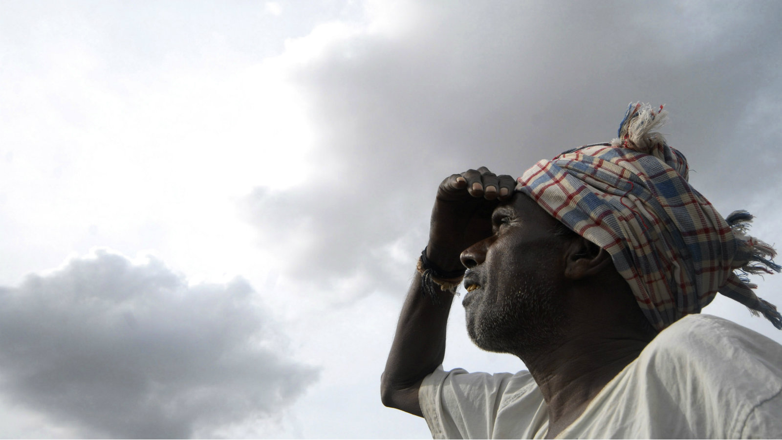 A farmer looks at louring monsoon clouds on the outskirts of Hyderabad, India, Monday, July 6, 2009. India will boost spending on irrigation and roll out more jobs and loans for farmers to spur the rural economy and lift farm sector growth to 4 percent, Finance Minister Pranab Mukherjee said presenting the new governments annual budget Monday.