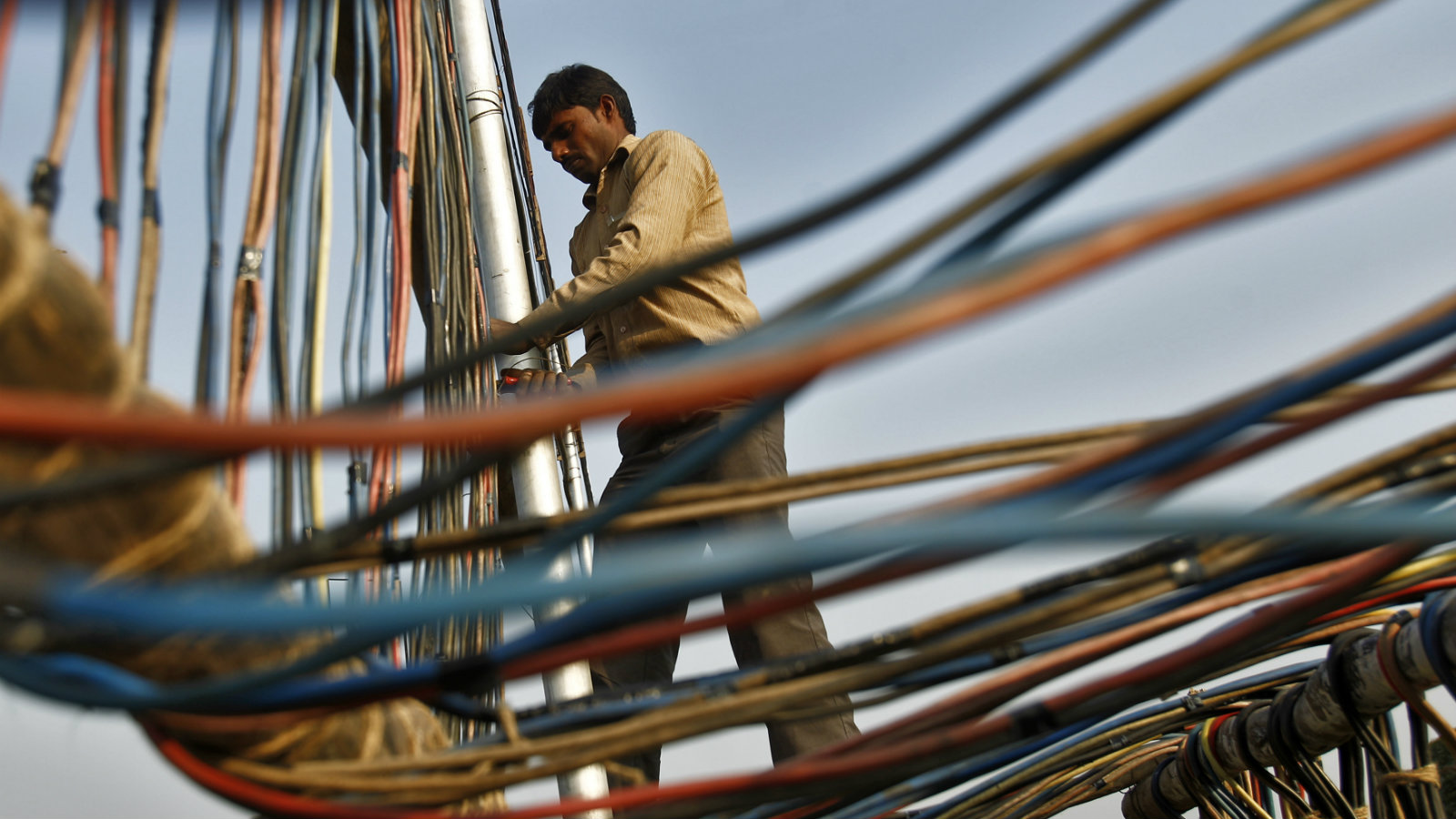 An electrician installs power cables outside the Indian Parliament building in New Delhi December 10, 2013.