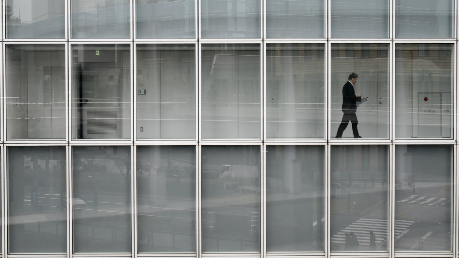 A man walks inside an office building in Tokyo March 19, 2014. Large Japanese firms are growing more confident about weathering the impact of an imminent sales tax increase and they expect further profit rises even after a bumper year, a Reuters poll showed - encouraging signs for an economy that is seeing a sharp slowdown in growth.