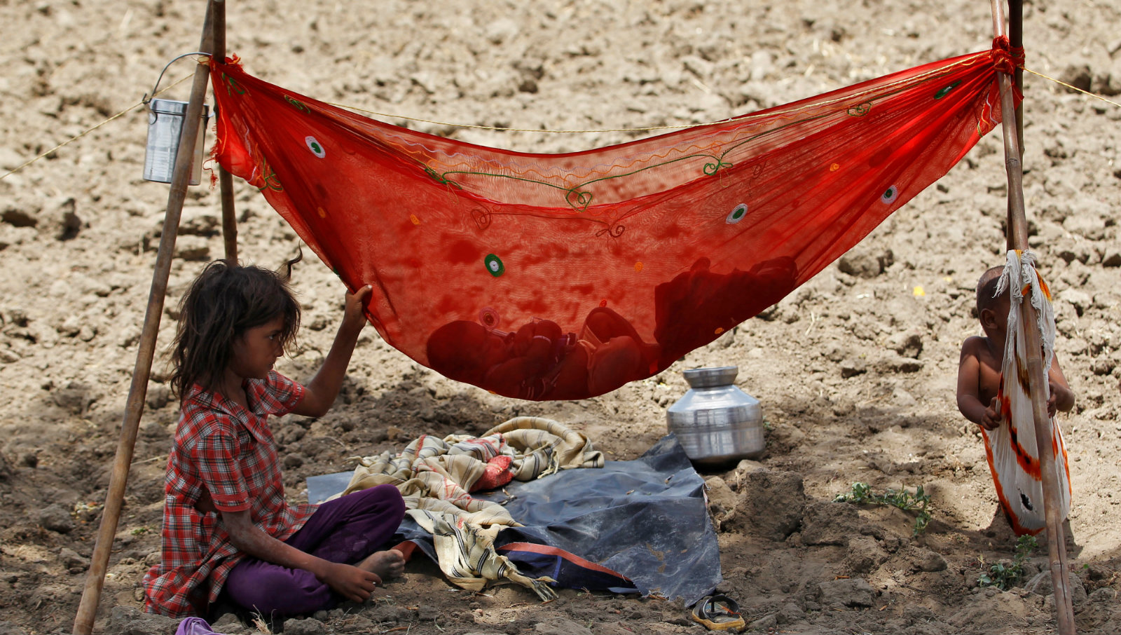 A girl sits next to her sibling who is resting in a hammock under the shade of a tree in a field on the outskirts of Ahmedabad, India May 31, 2016.