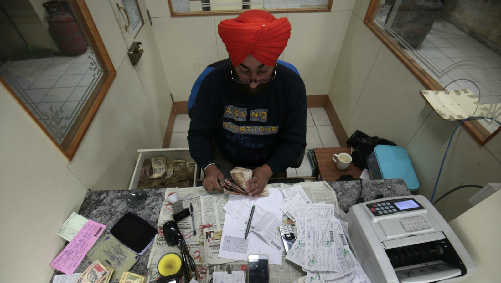 A bank executive counts discontinued 1000 Indian Rupee notes at a bank in Srinagar, the summer capital of Indian Kashmir, 10 November 2016. In a major decision, Indian Prime Minister, in an address to the nation has stated that currency notes with denomination values of INR 500 (about 7.5 US dollars) and INR 1000 (about 15 US dollars) respectively will be invalid and will be discontinued from midnight of 08 November 2016. Indian government also introduced the new notes of INR 500 (about 7.5 US dollars) and INR 2000 (about 30 US dollars) and citizens would be allowed to exchange their old currency notes through the banks and post offices till 30 December 2016. This is being considered as a major step towards curbing the problem of black money.