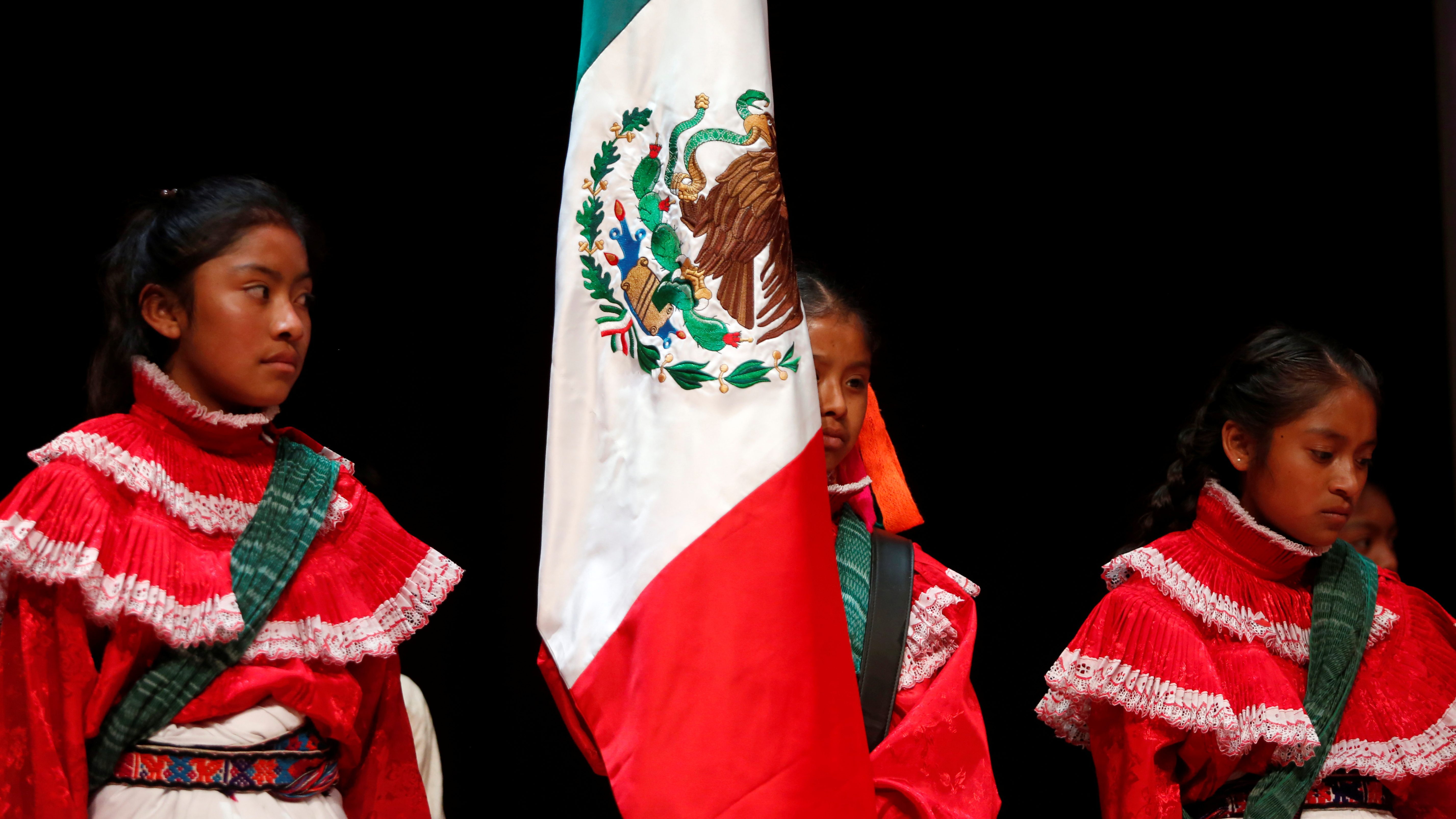 Indigenous children stand next the Mexican flag