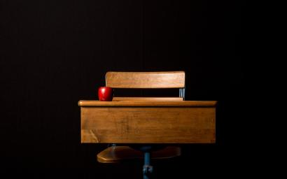 A red apple sits on a wooden desk in front of a black backdrop.